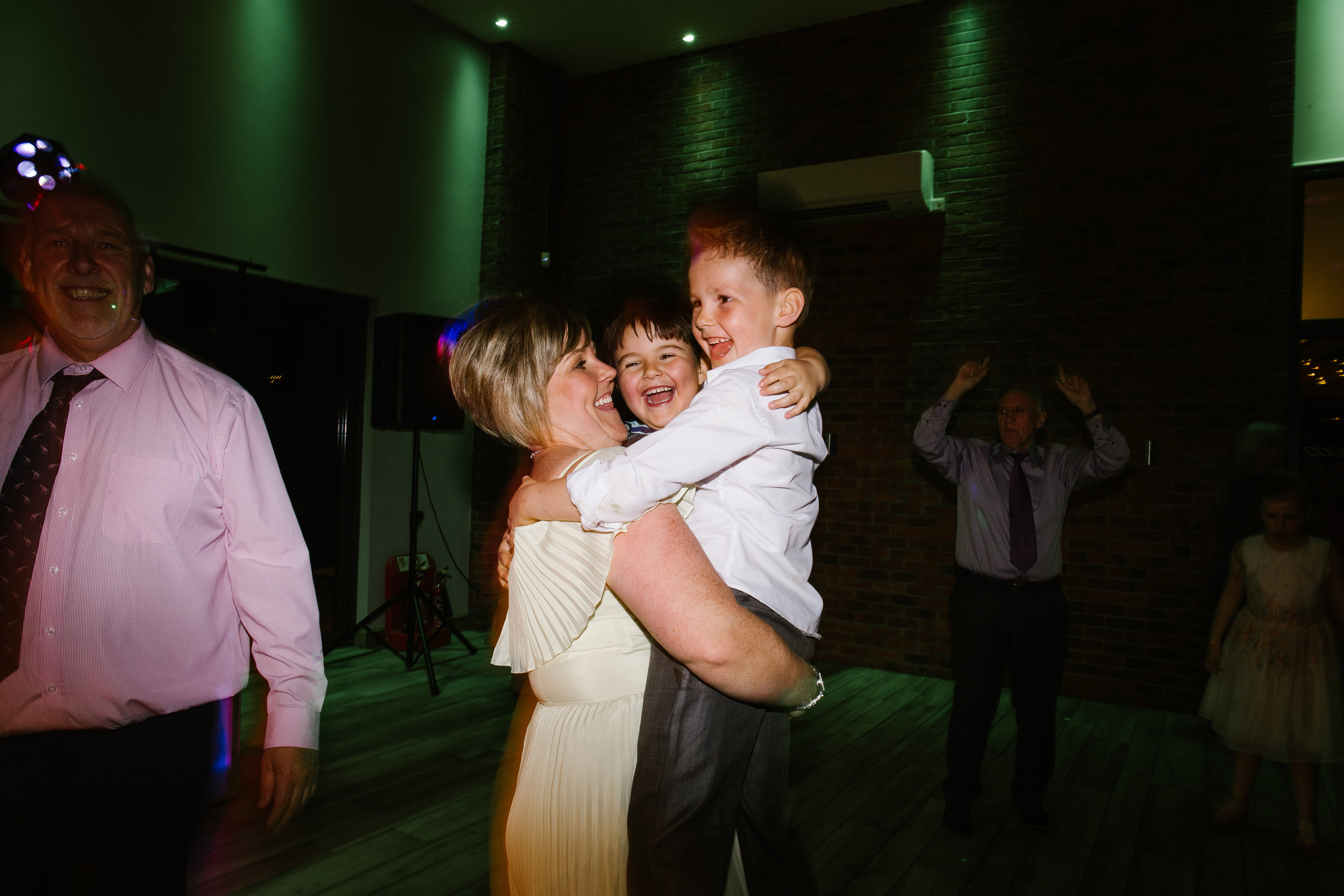 bridesmaid holding two small children as they laugh and dance together on the dance floor