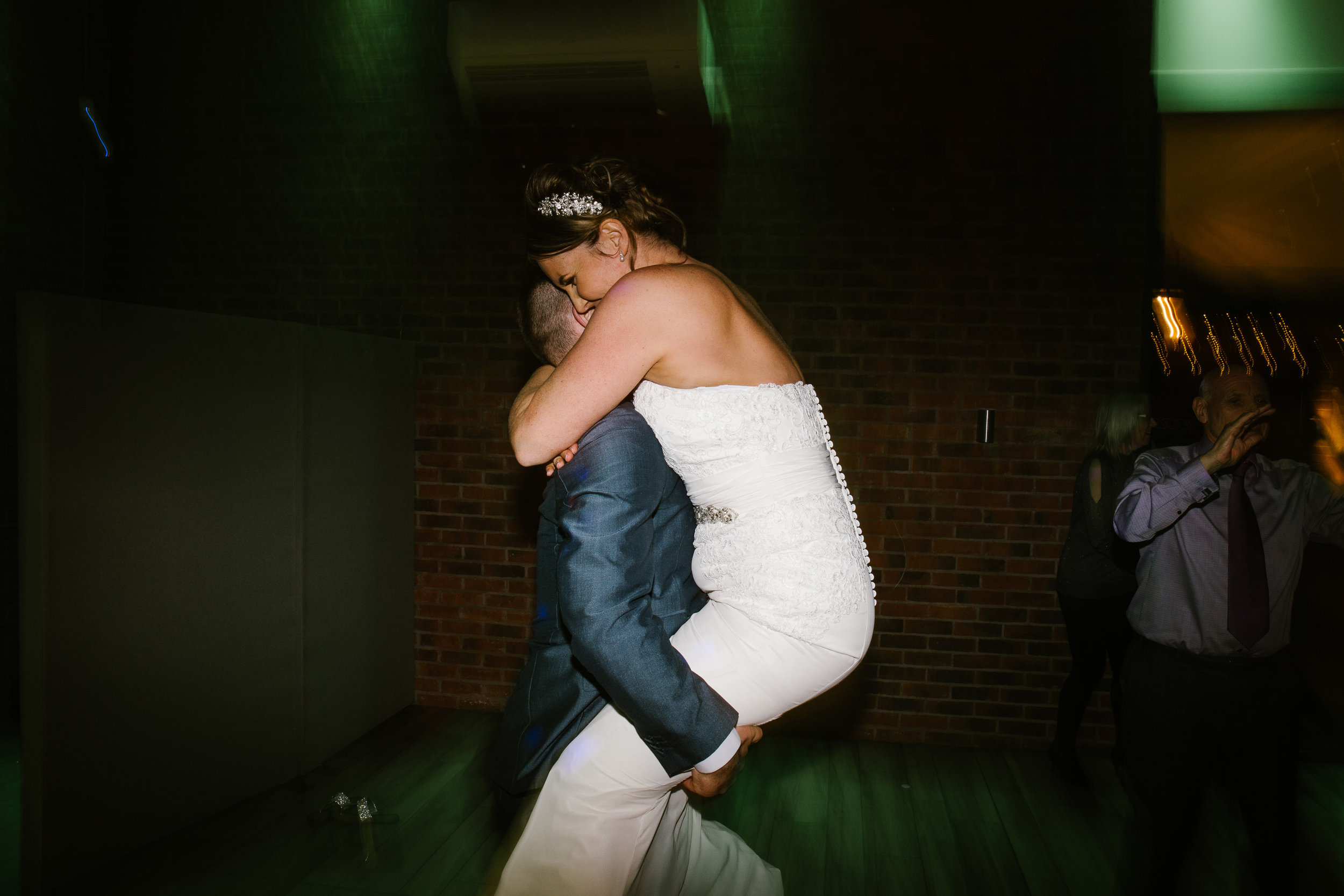bride jumping up into husbands arms as they dance on the dance floor together