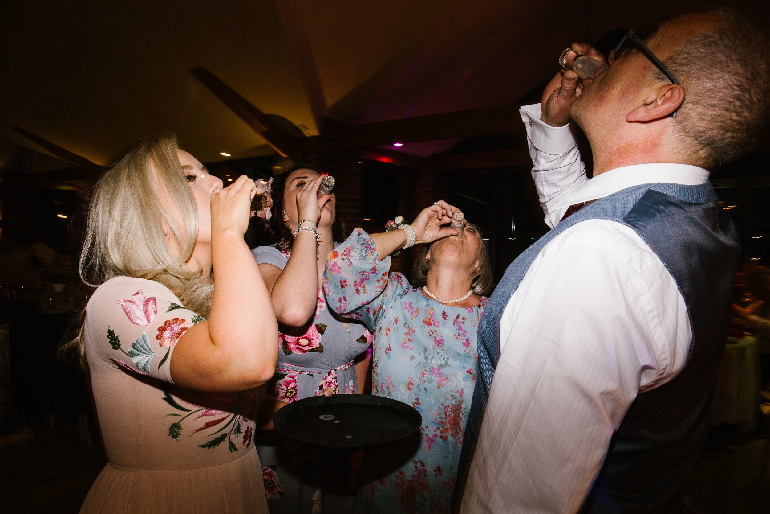 wedding guests and the mother of the bride doing shots on the dance floor at the wedding party
