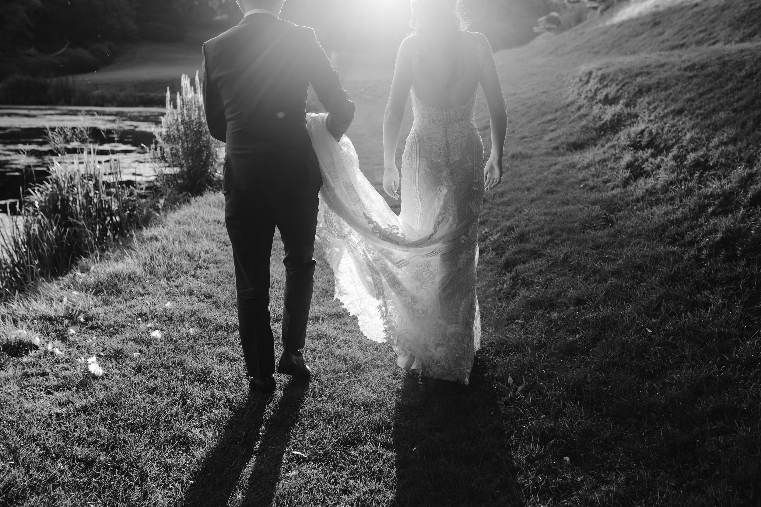 a natural silouette of the bride and groom walking together in the golden light in the grounds at cowley manor in the cotswolds