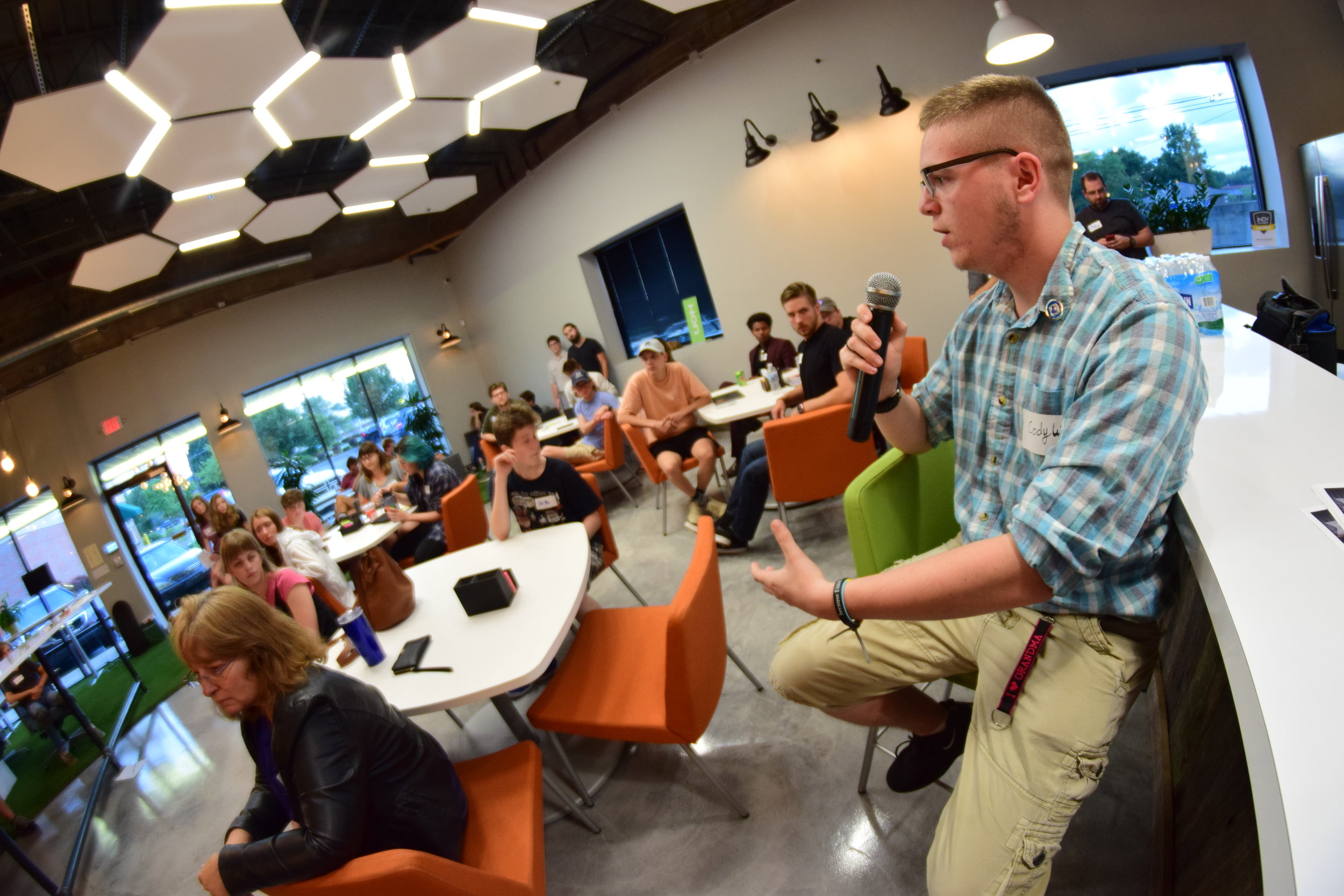Cody Wysong with the microphone at a Student Innovation Night at Outhouse Coworking