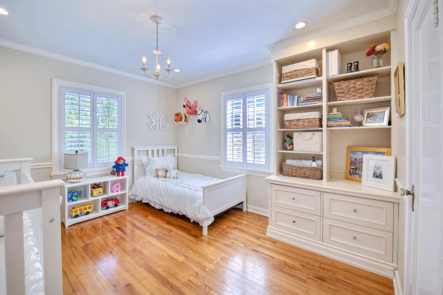 """Kids Room: After! We repurposed those beautiful built in's! I never got around to """"finishing"""" this room (hanging curtains, adding an area rug, changing quints crib bedding to be gender appropriate *he uses all of Sutton's things*, etc.) But, it was a sweet little room for them. I love the little chandelier we added, too."""