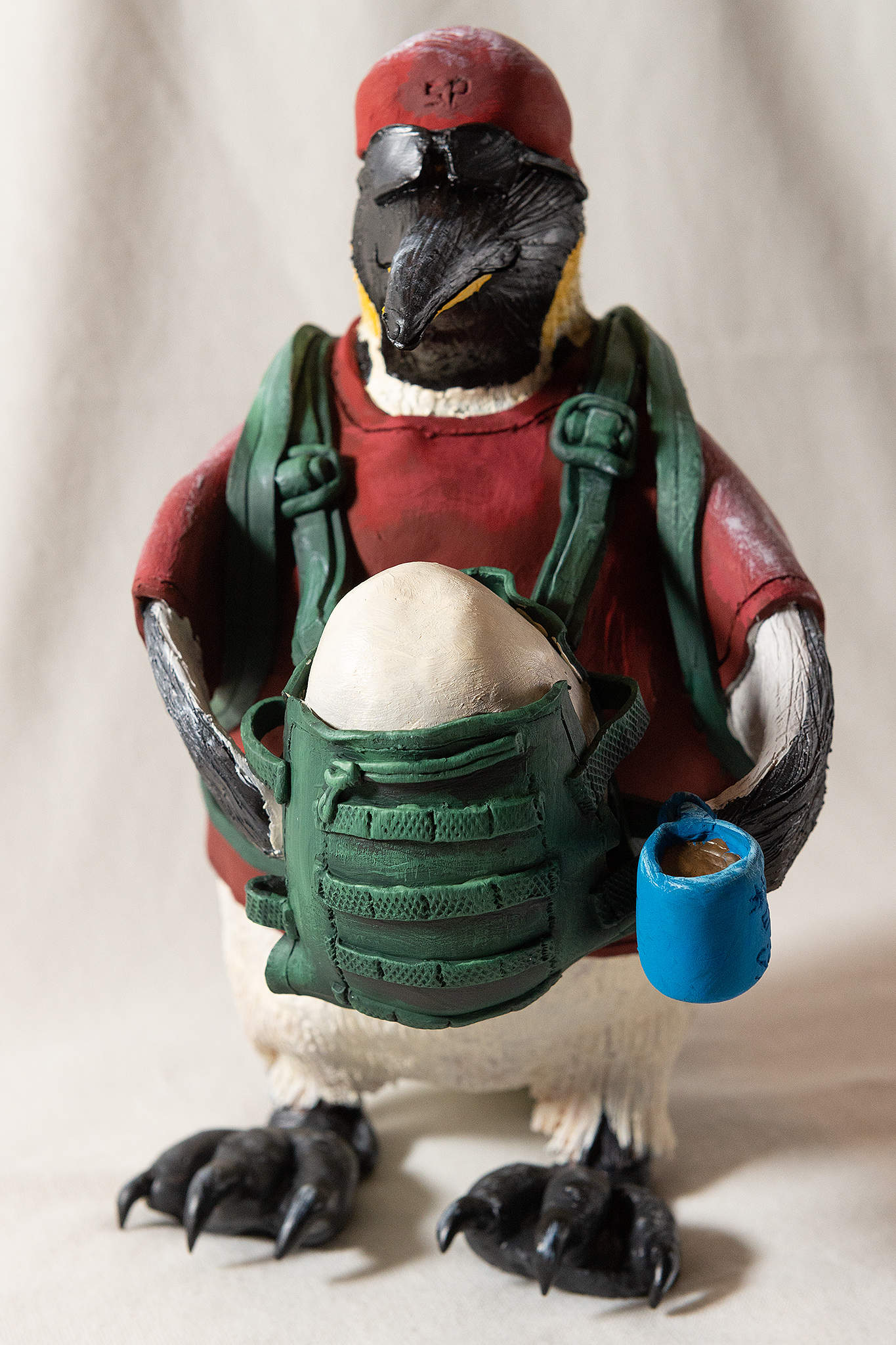 Penguin dad character with coffee and egg in baby carrier