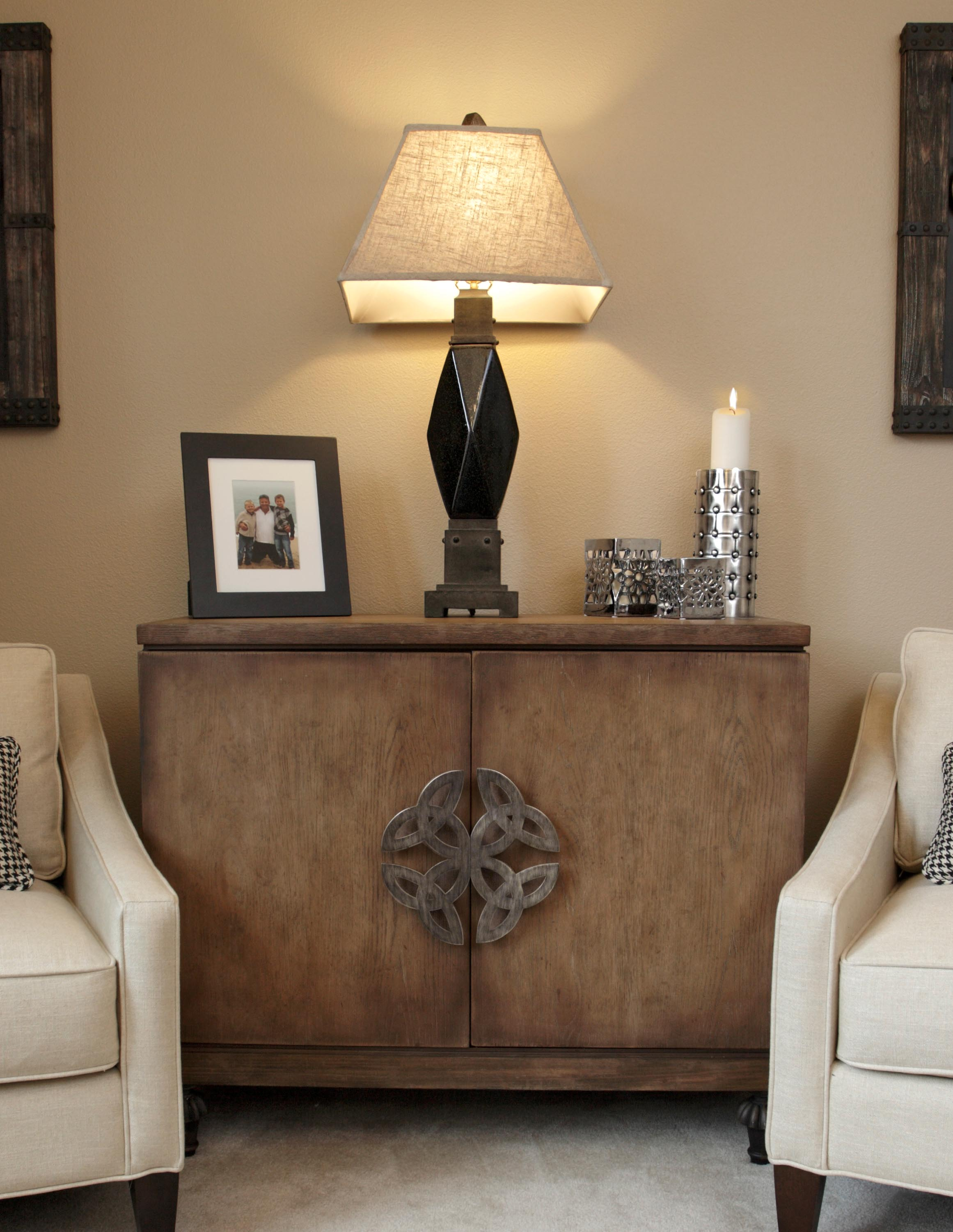 Elegant picture frame, lamp and candle above the cabinet