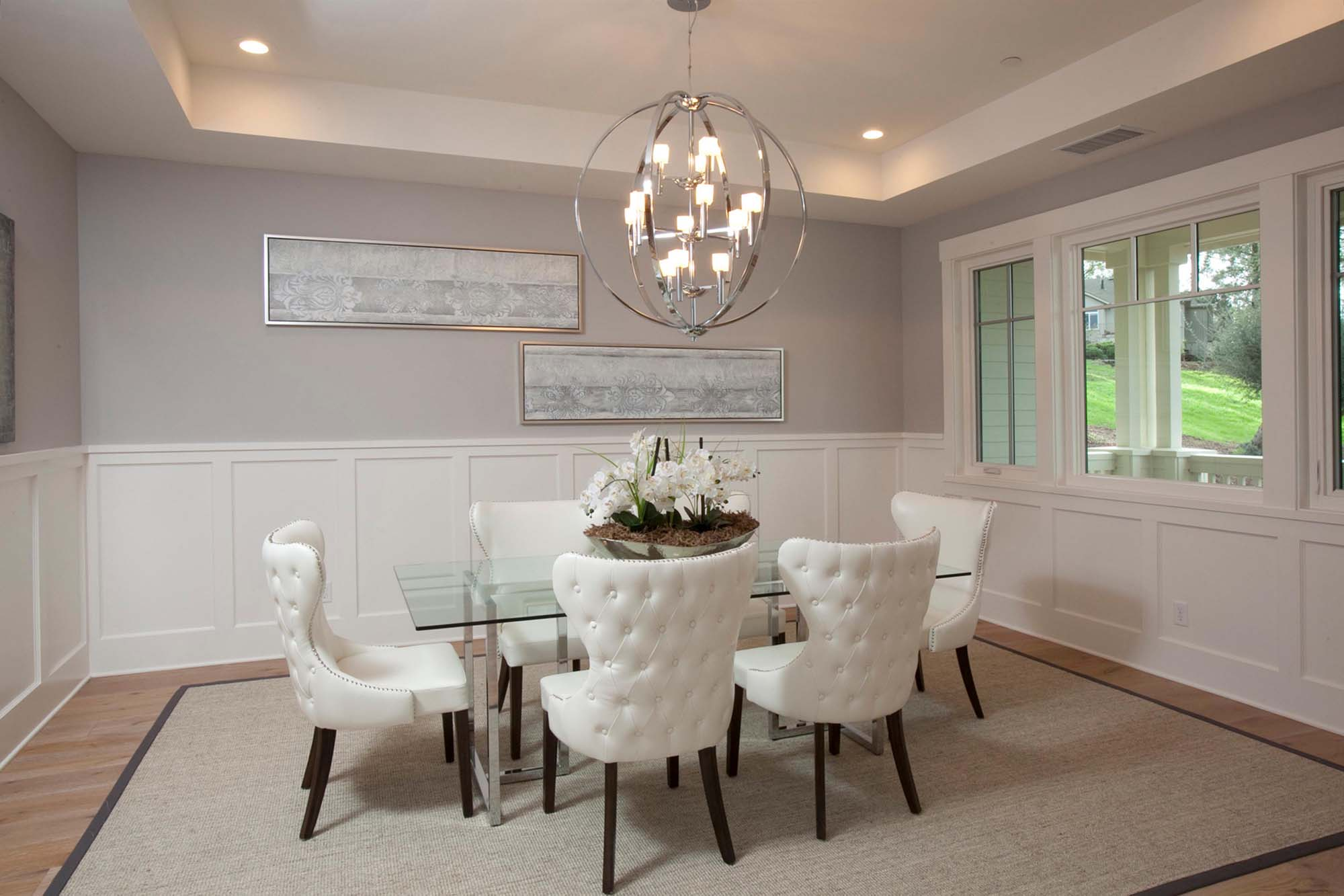 Modern living room with sets of chairs, table and chandelier