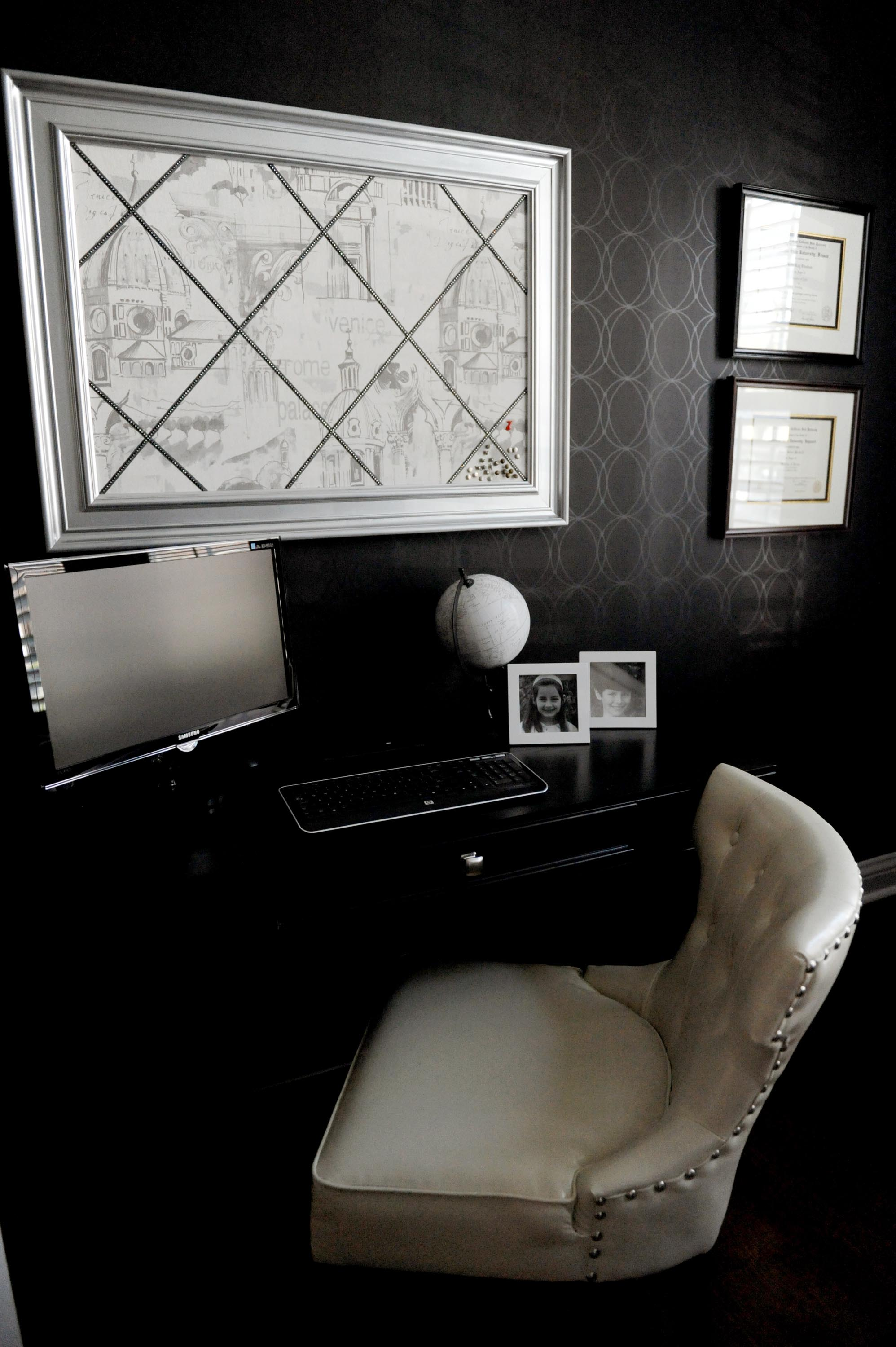 Elegant home office with black wall and a computer