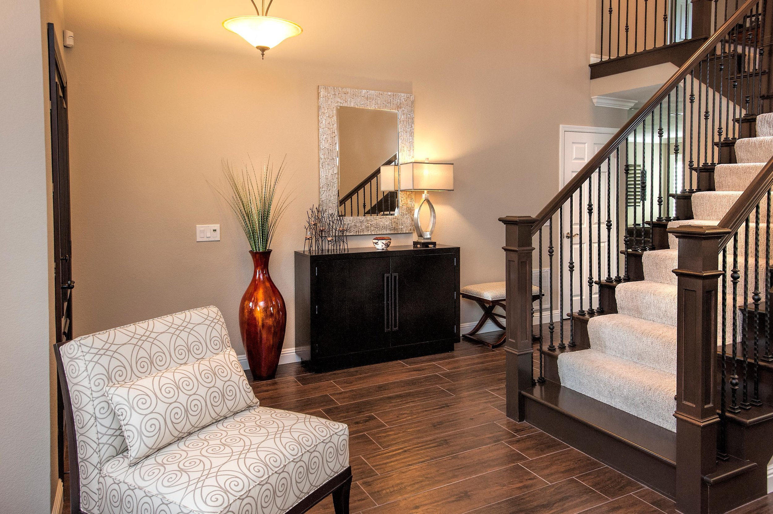 Stylish mirror, lamp, flower vase, cabinet and stairway with a sofa