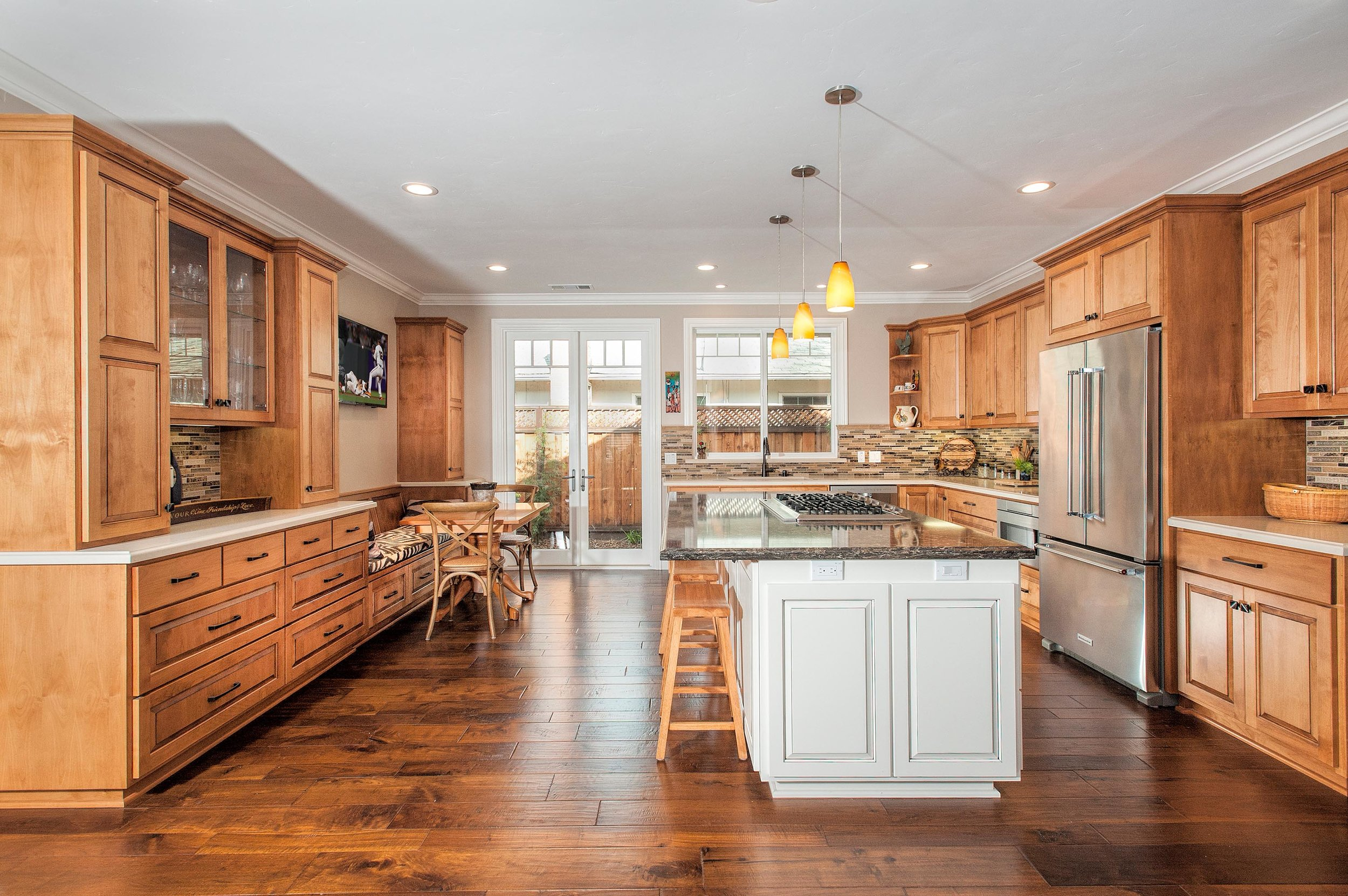 Elegant kitchen with wood look tile flooring and island in the center
