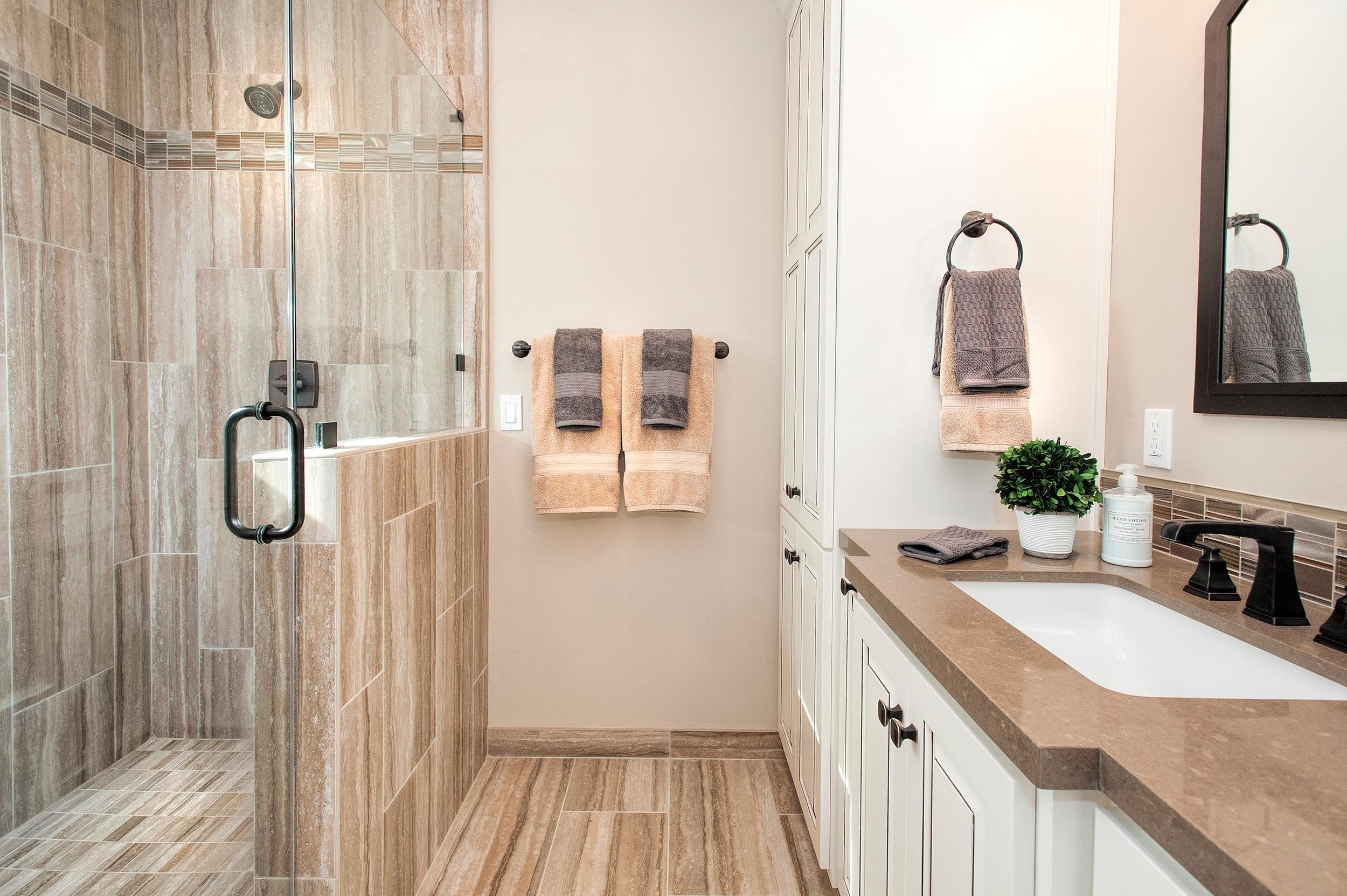 Stylish bathroom with mirror, faucet and wood look tile flooring