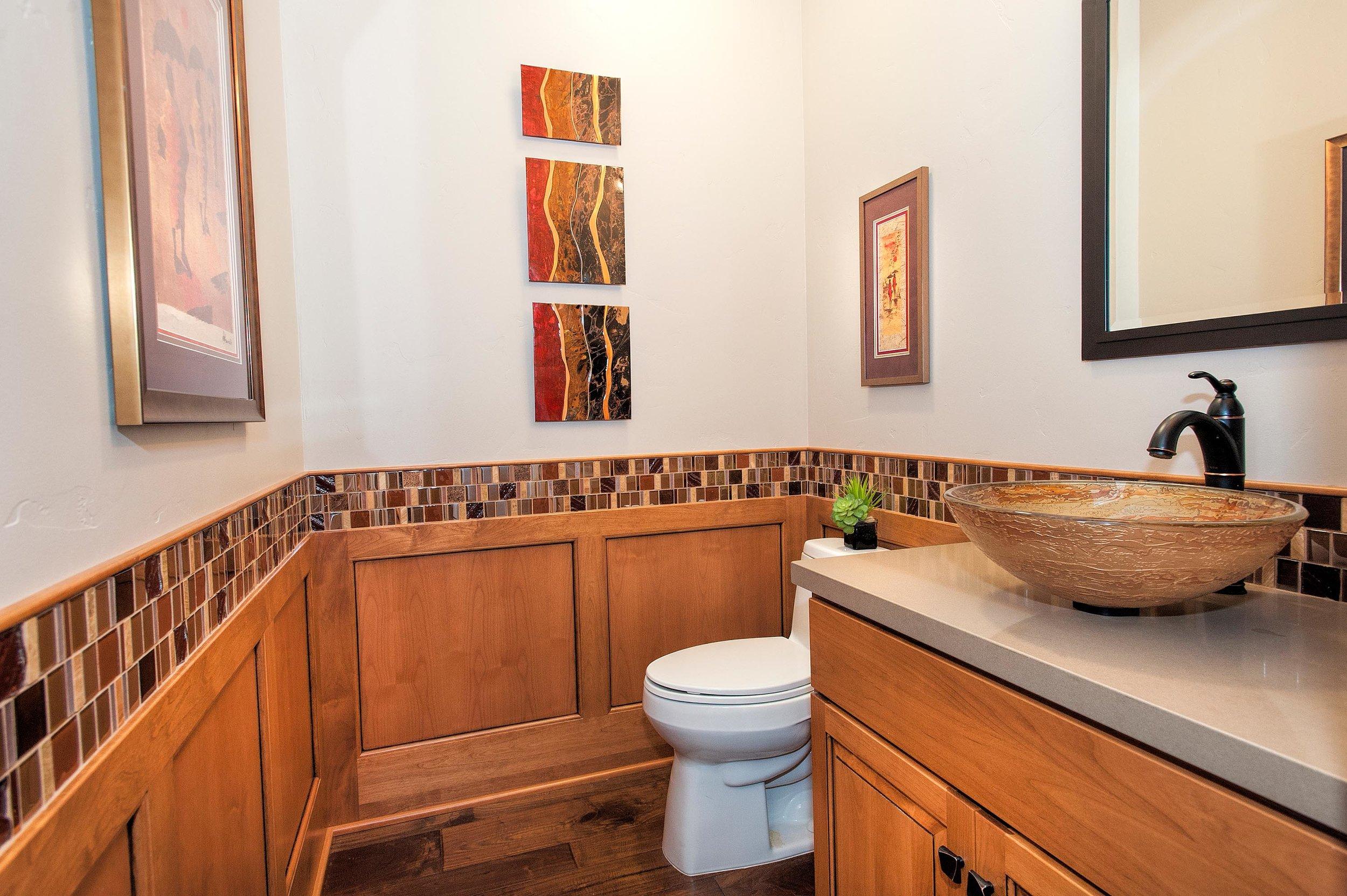 Elegant bathroom with wood look tile flooring, painting and cabinet