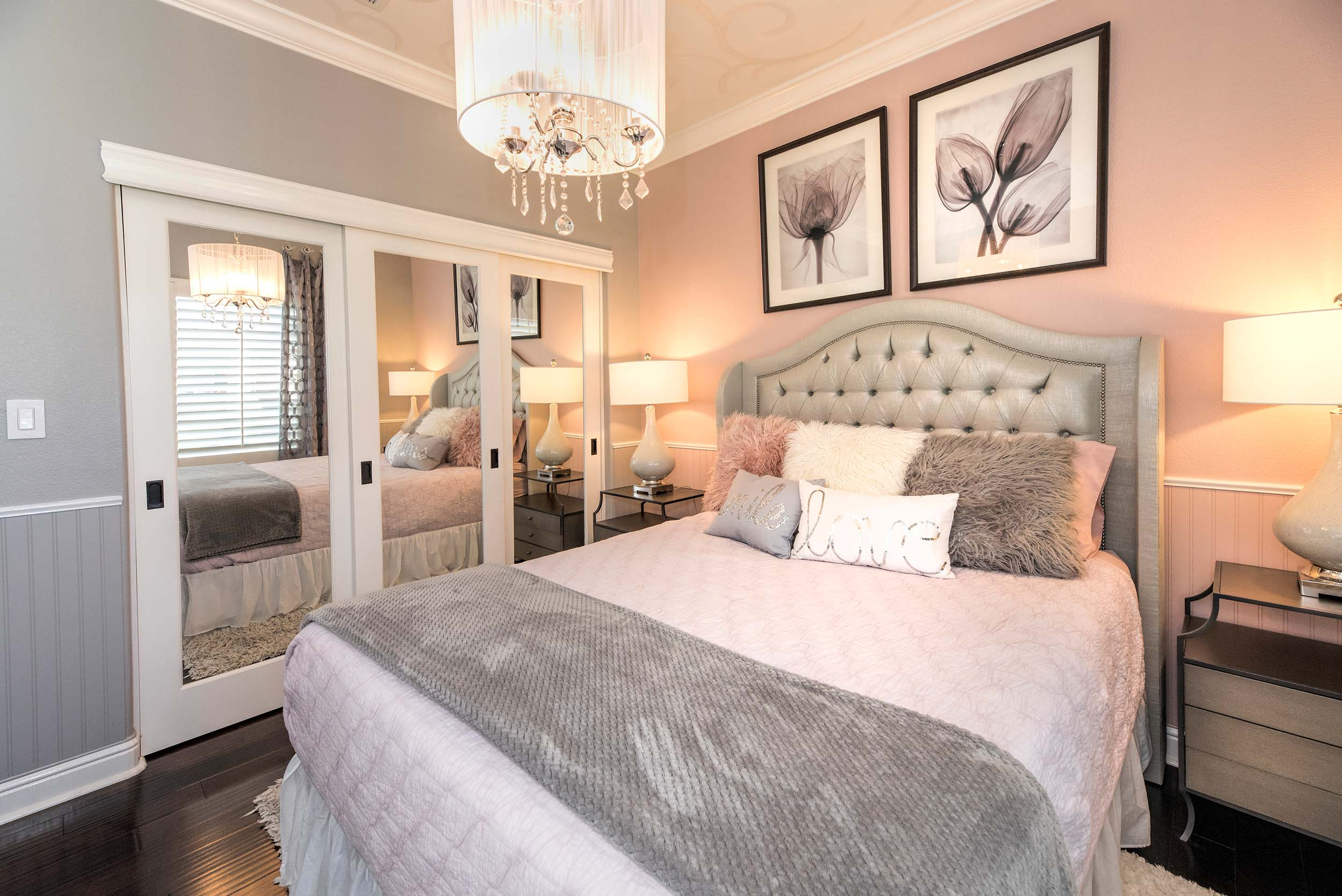 Bedroom with large bed, mirrored door cabinet, chandelier and frames on wall