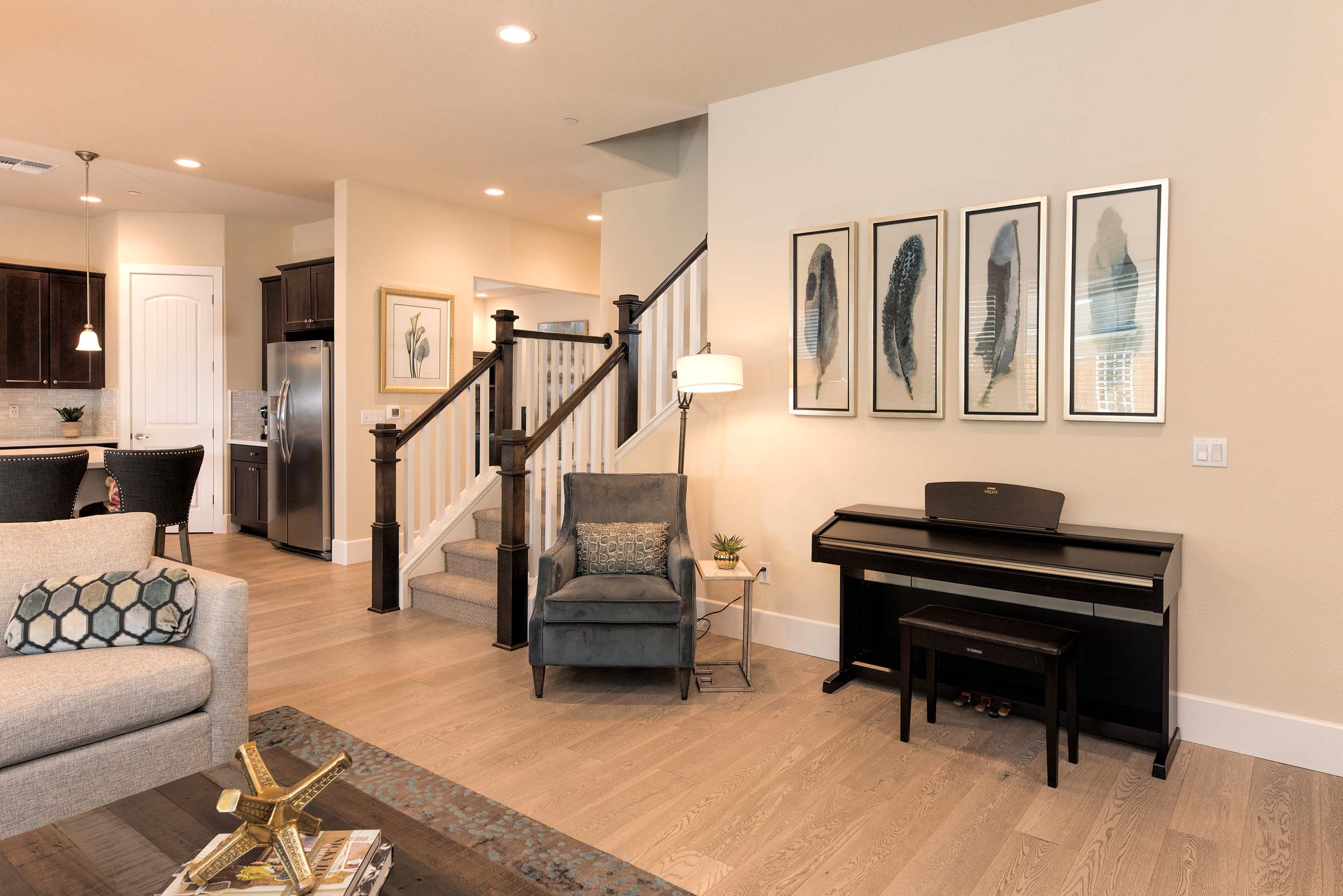 Modern living room with hardwood floor, grand piano, staircase and frames on the wall