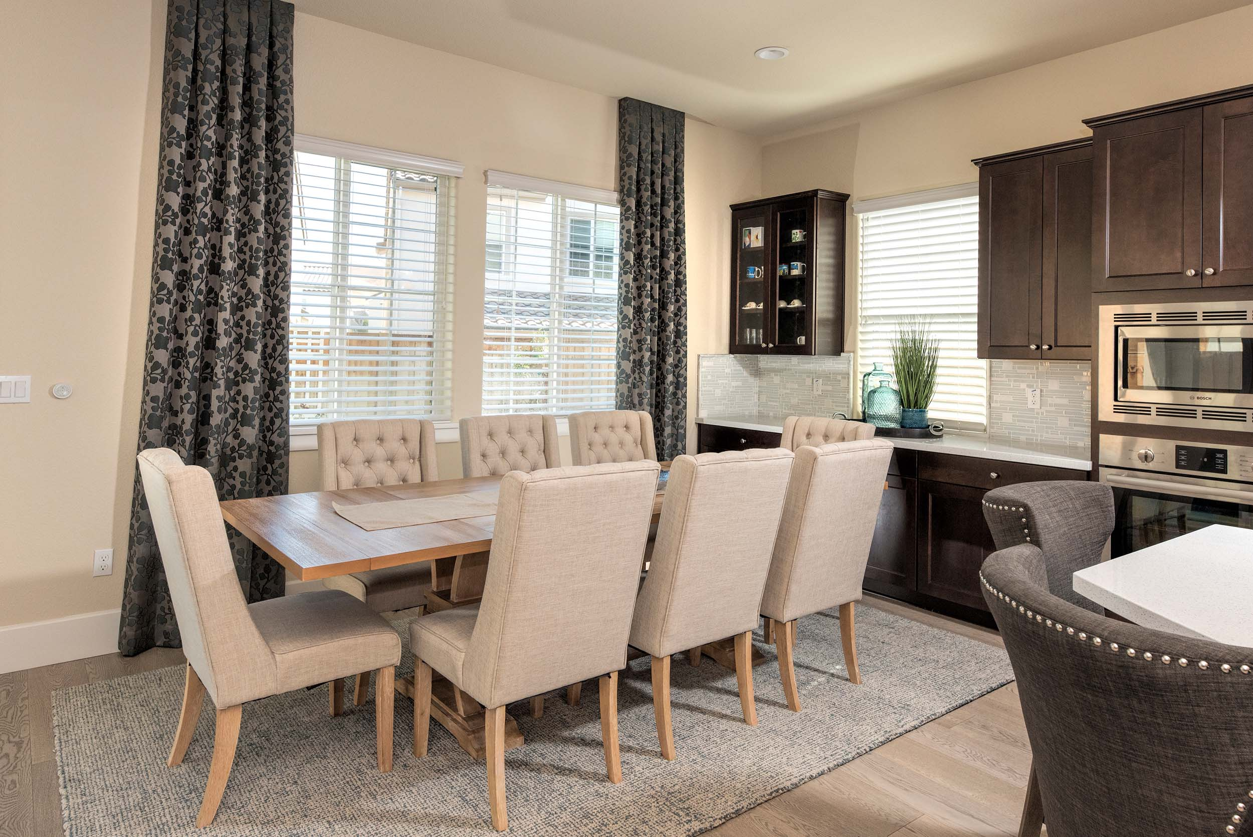 Dining room with chairs, wooden table, hardwood floor, and wooden cabinets