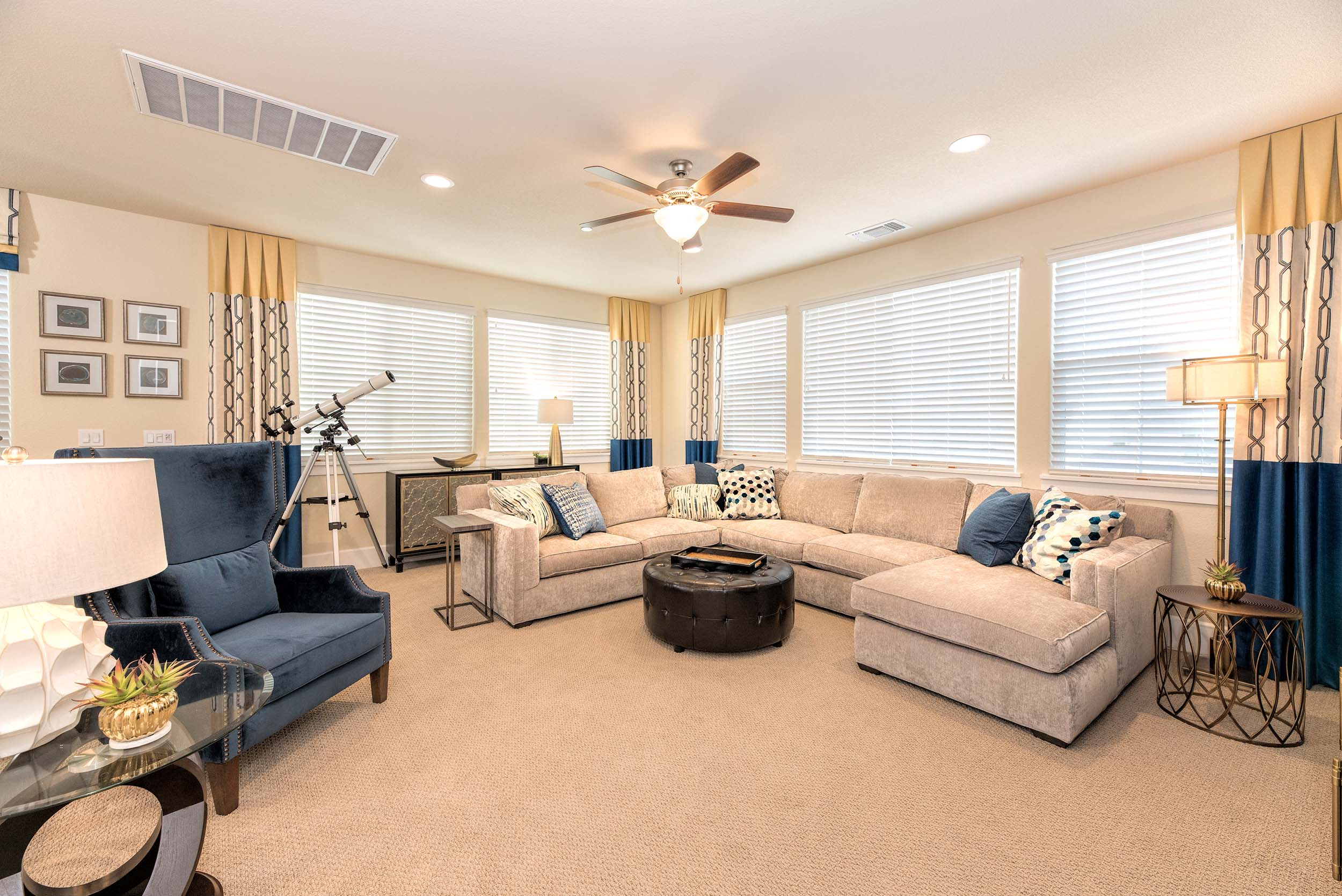 Living room with sofa, large windows and ceiling fan