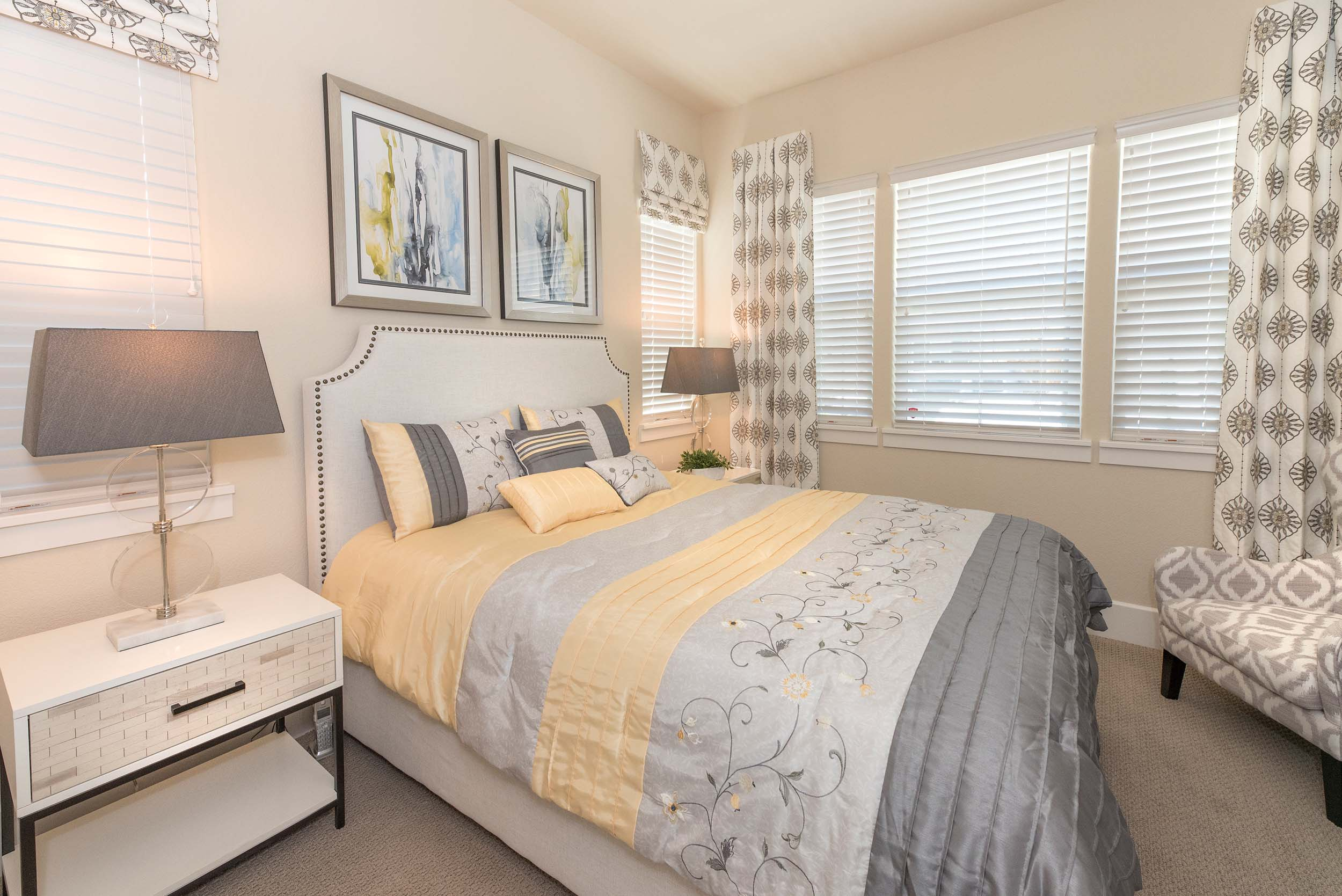 Bedroom with bedside table, table lamps and frames on the wall