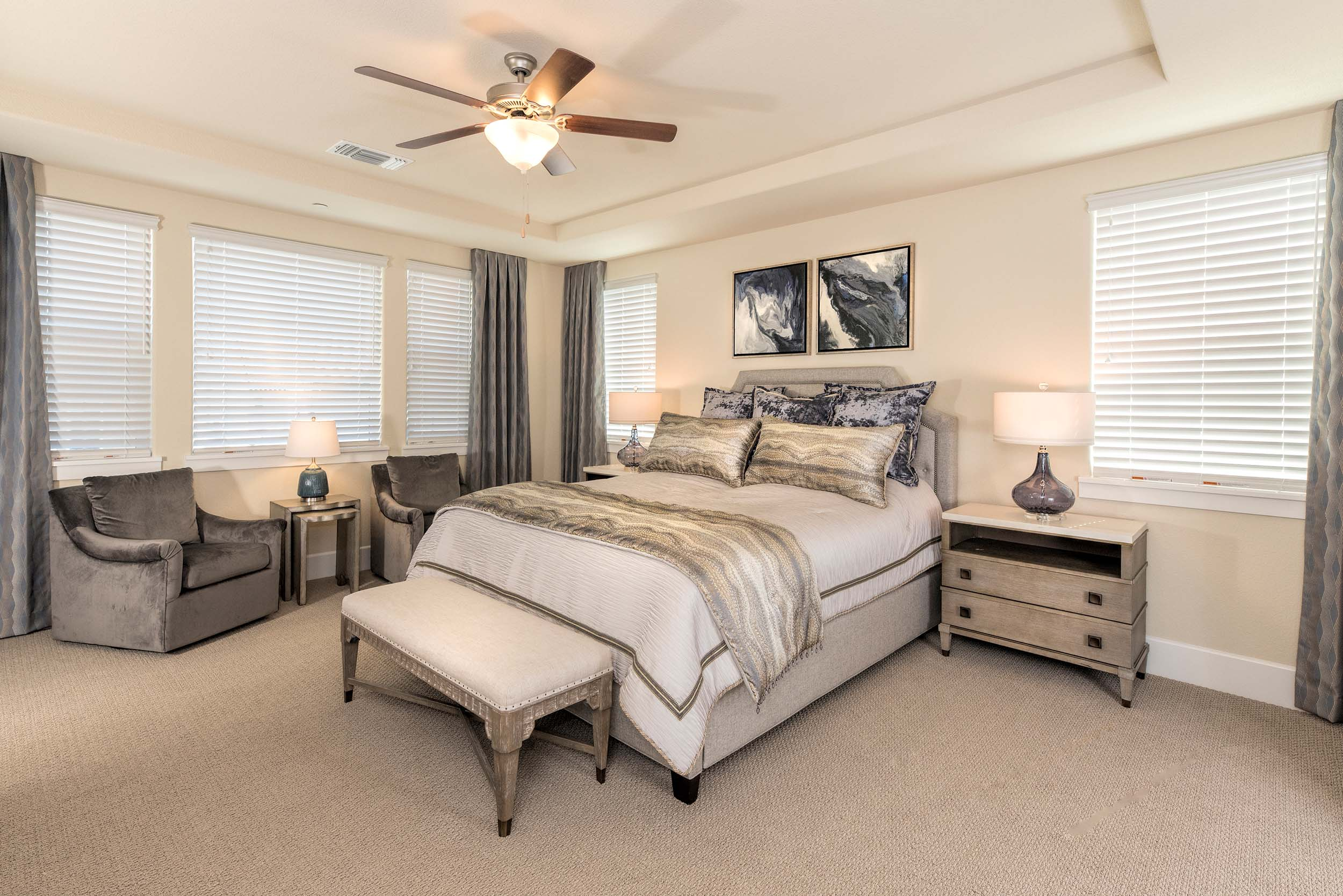 Modern bedroom with bed, bedside table, table lamps, ceiling fan and armchair