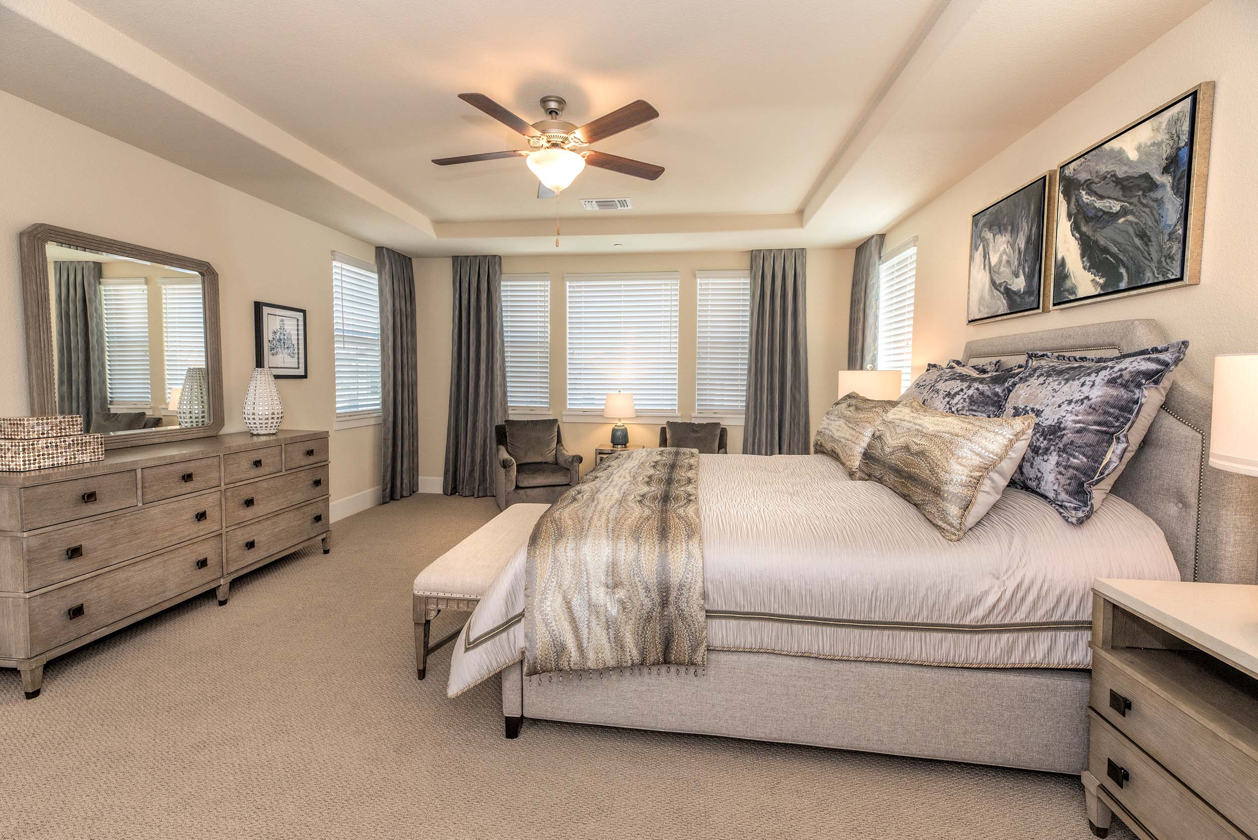 Bedroom with bed, large drawer, mirror and ceiling fan