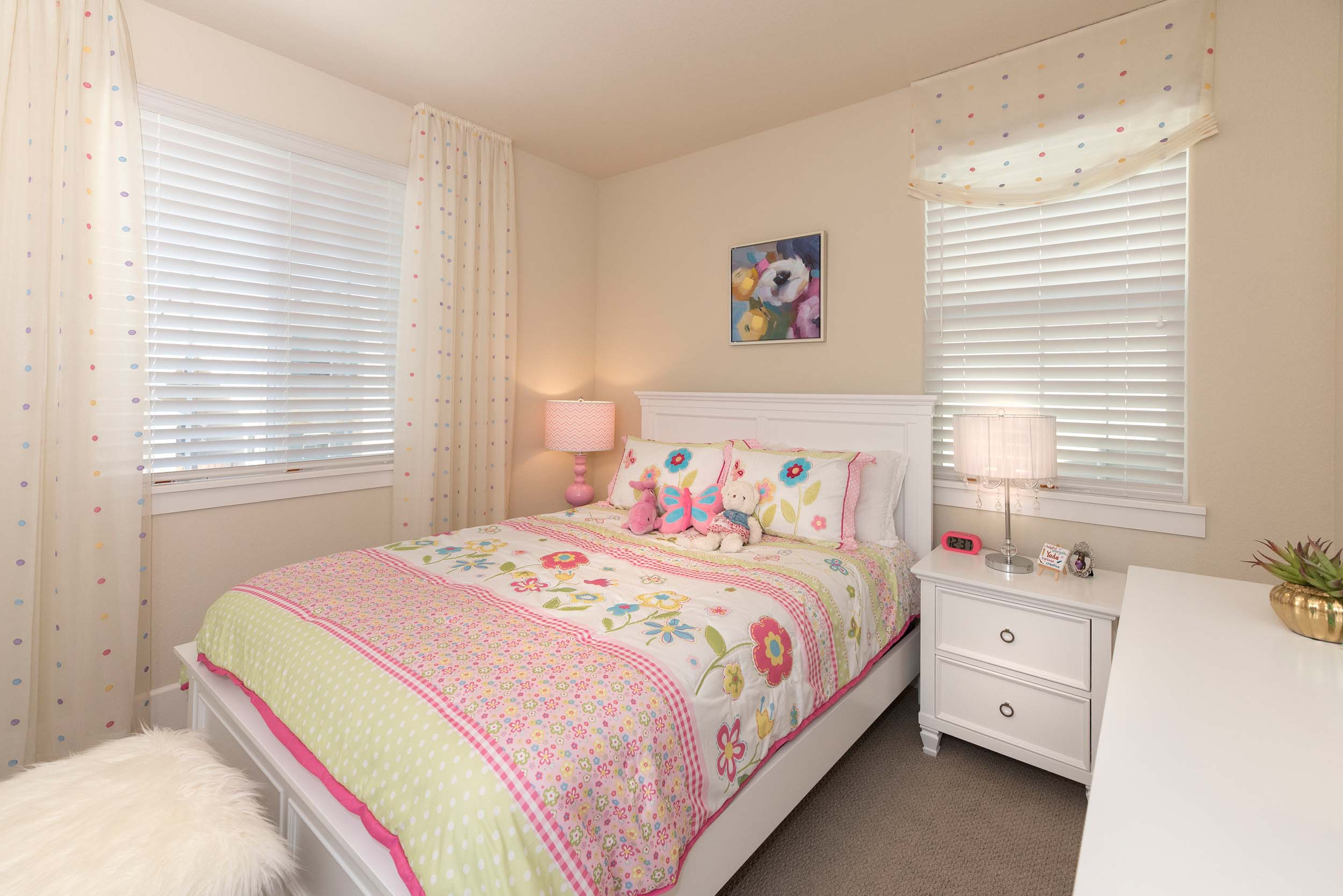 Small bedroom with pink bedsheet, bedside table and table lamps
