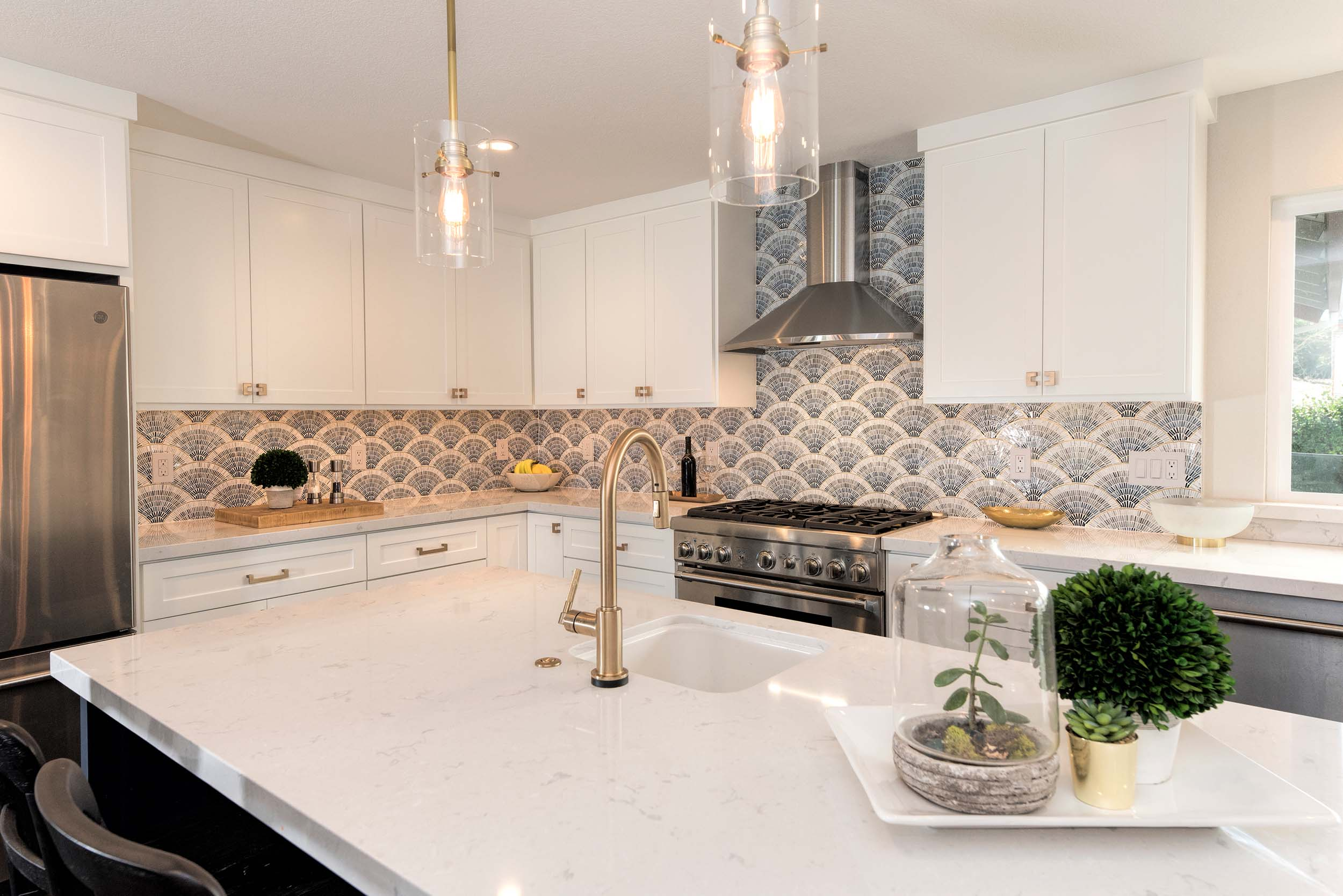 Kitchen with center island, faucet, granite countertop, exhaust hood and white wooden cabinet