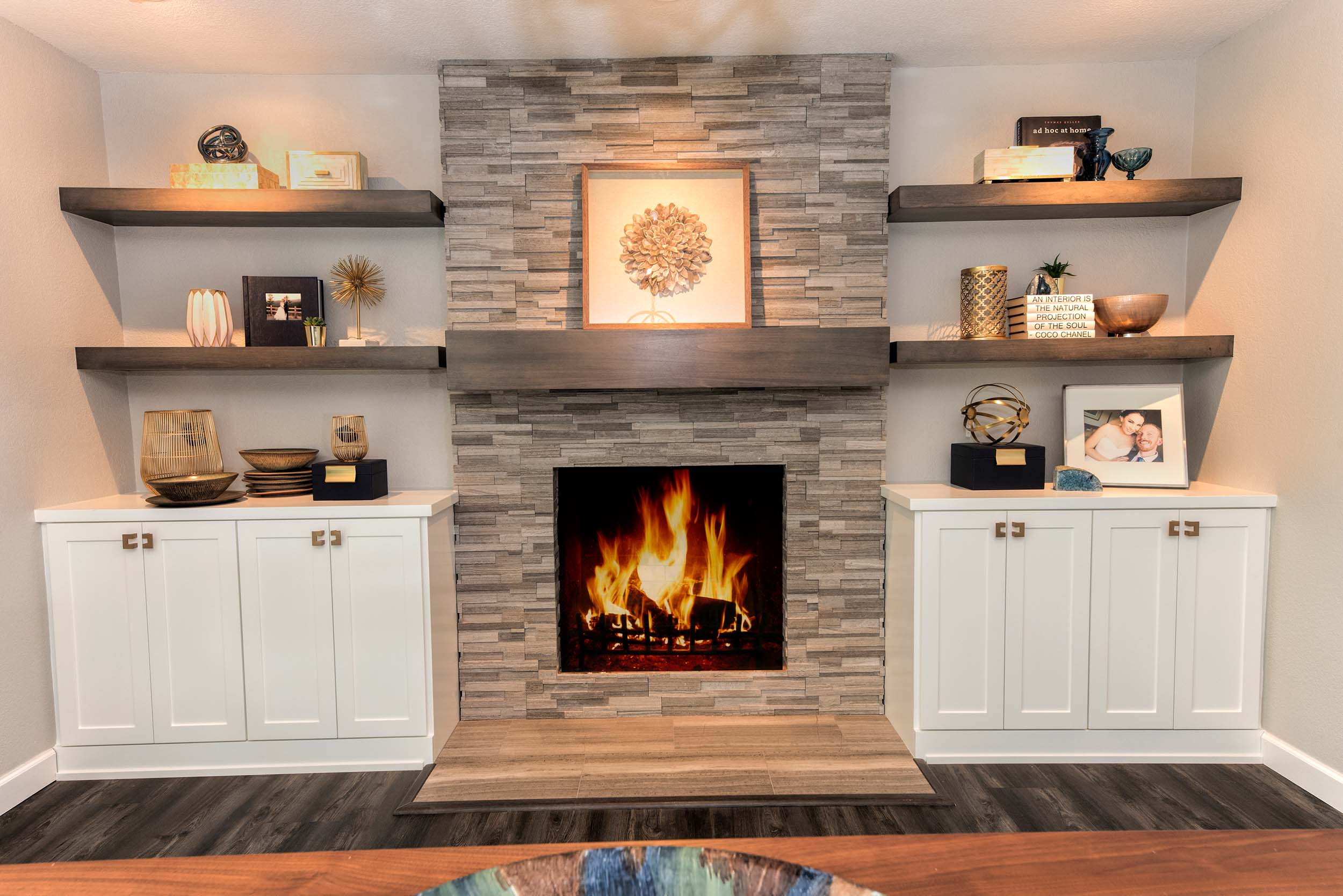 House interior with stone fireplace, hardwood floor, built-in shelves and cabinet