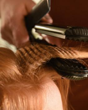 Tutoriel coiffage – Etape 1   Lisser les cheveux au brushing. Réaliser une séparation à droite en partant du milieu de l'œil jusqu'à l'occipital. Pratiquer de même à gauche. Gaufrer toute les racines jusqu'à 10 cm de cette séparation