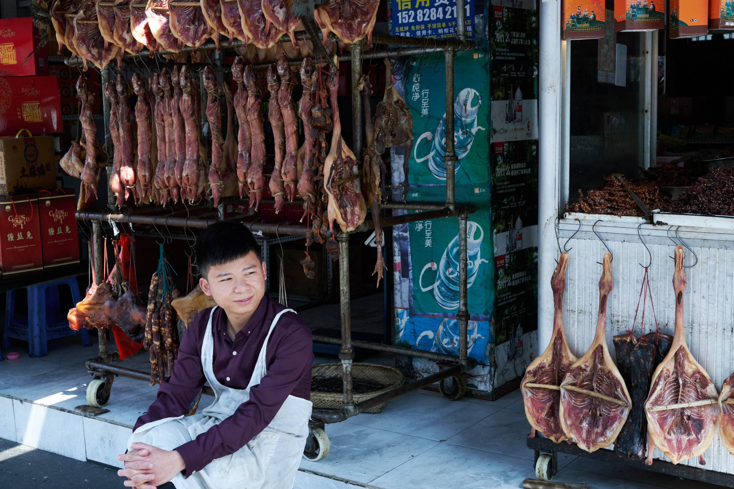 Vendor in Guanghan with red rabbit and other cured meats