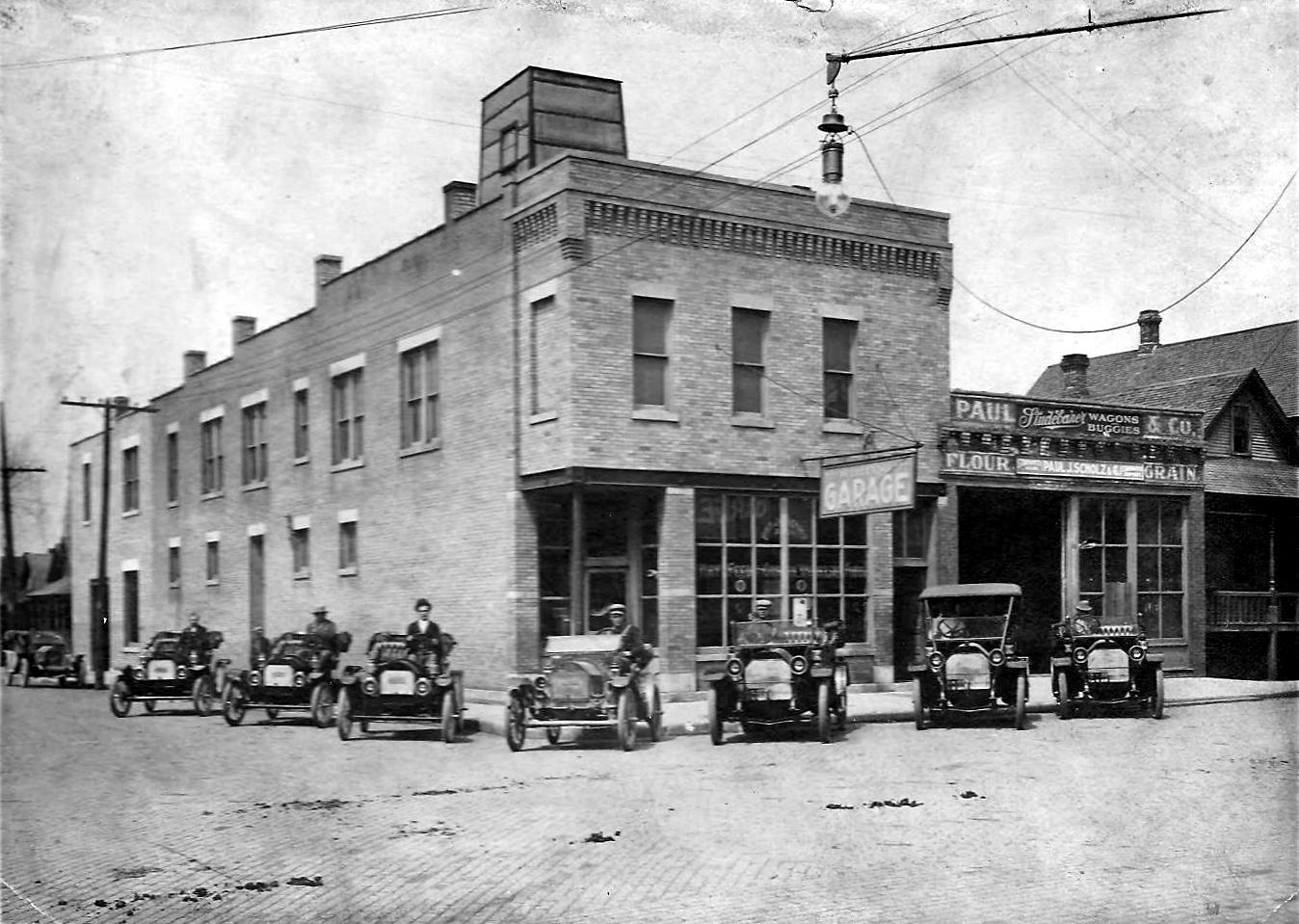 A group of drivers pose with their cars outside of the Whiting Garage at the northwest corner of New York and Fischrupp Avenues. The garage was a part of the Paul Scholz Wagons & Buggies Company. Paul Scholz's flour and grain store also operated at this site.