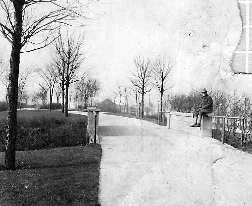 A soldier, back from the war, sits on a wall in Whiting Park.