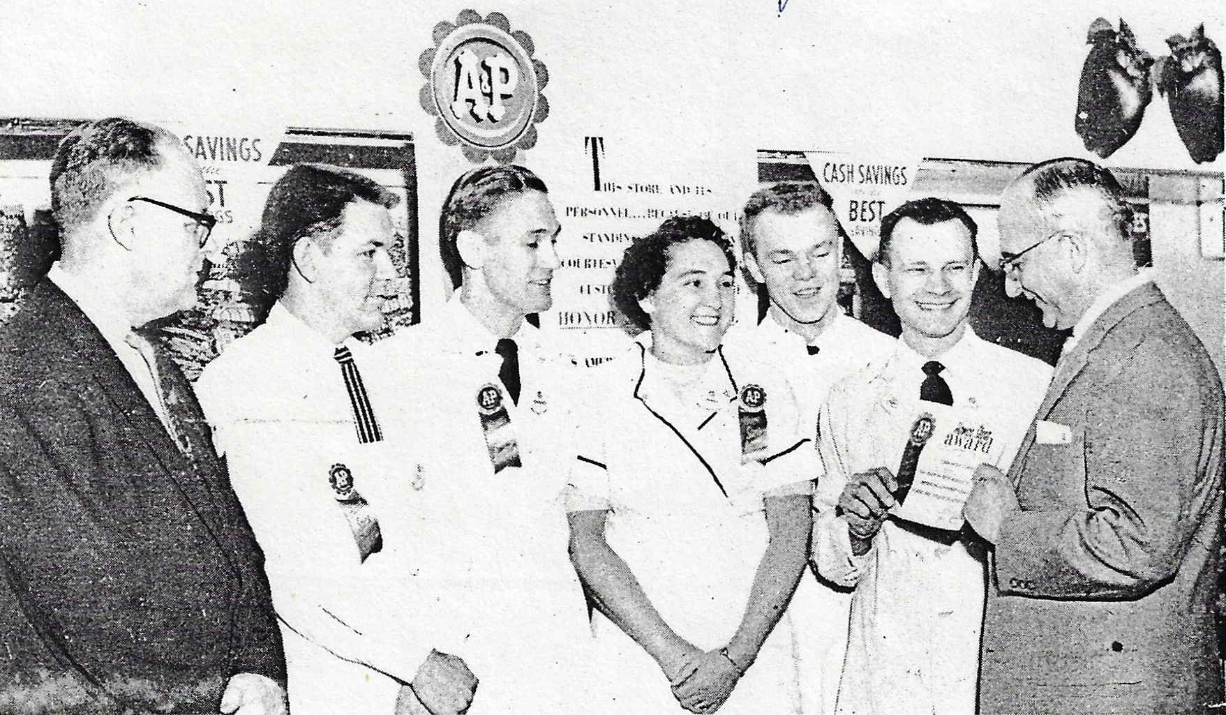 A&P Whiting employees accept an award for all employees for outstanding courtesy and customer service in 1958. From left to right are F. Kettles, district superintendent; Donald Utterback, assistant store manager; Clarence Goranowski, head of meat department; Mary White, cashier; Steve Krajnik, produce department; Mike Yaros, store manager; and K. Stitzer, Southside general superintendent of the A&P Company, Chicago.
