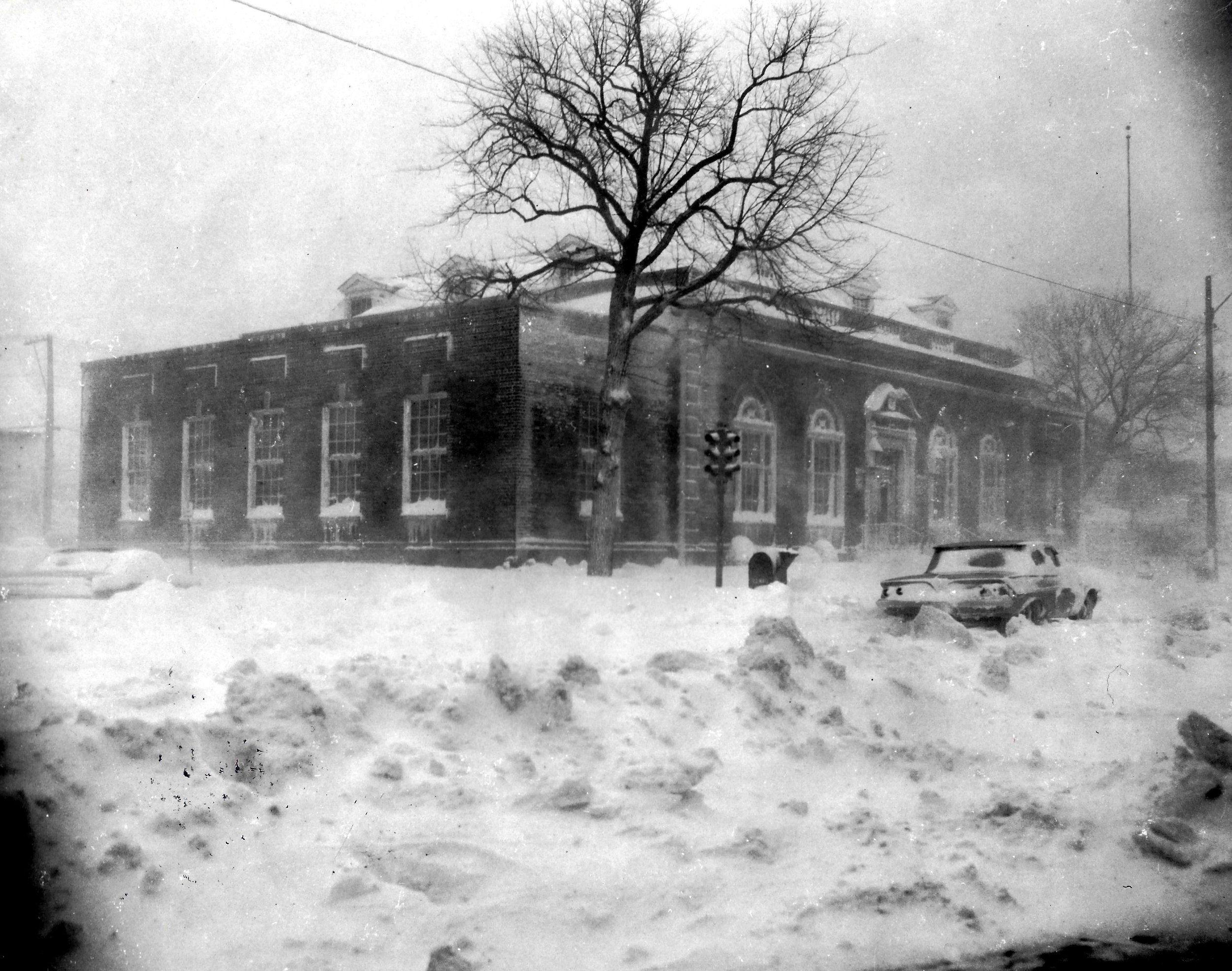 Snow piled up at 119th Street and New York Avenue, with the Whiting Post Office in the background, a stranded car to the right.