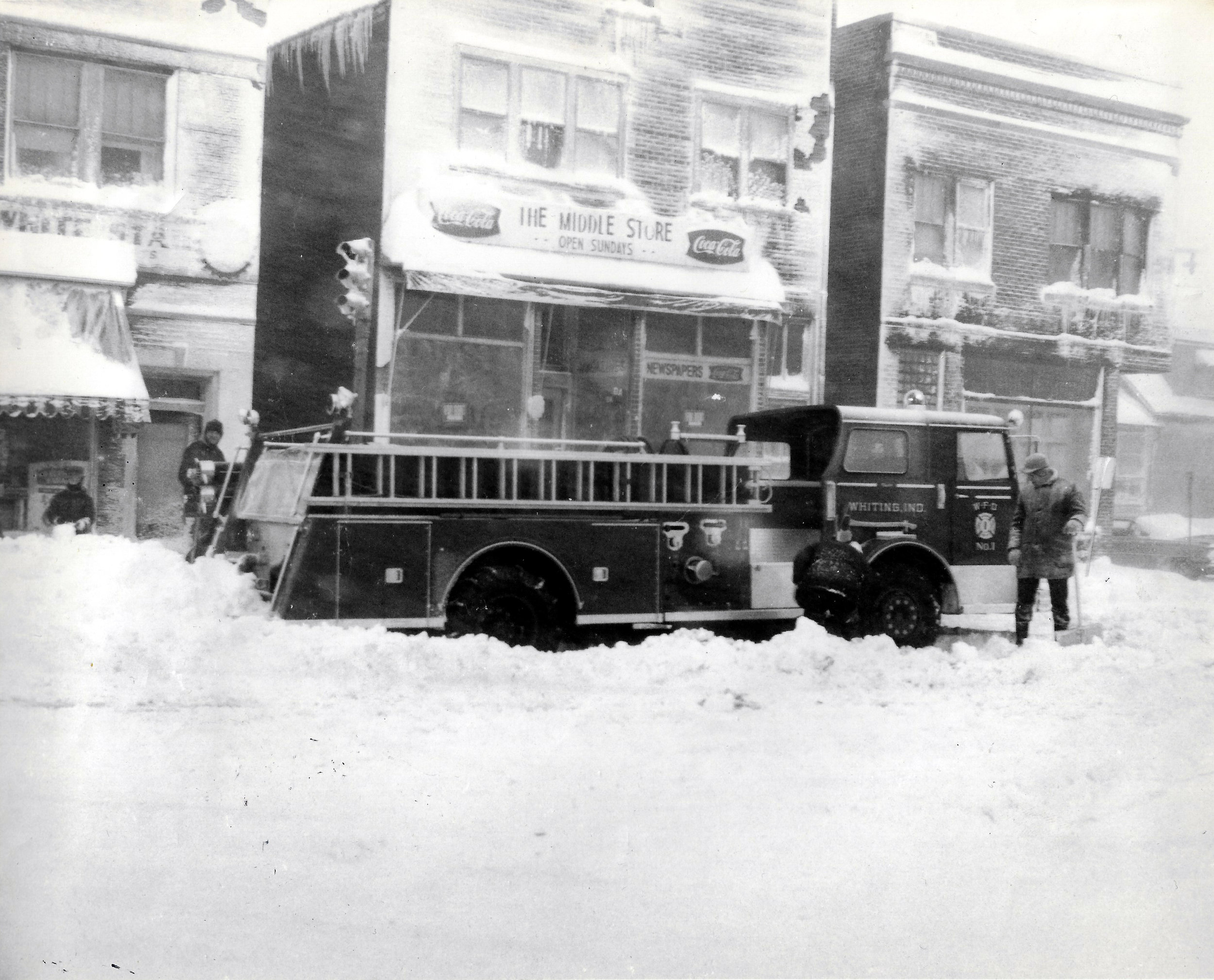 A Whiting fire truck deals with the snow on 121st Street, just east of Indianapolis Boulevard, while snow clings to the façade of the shops behind it.