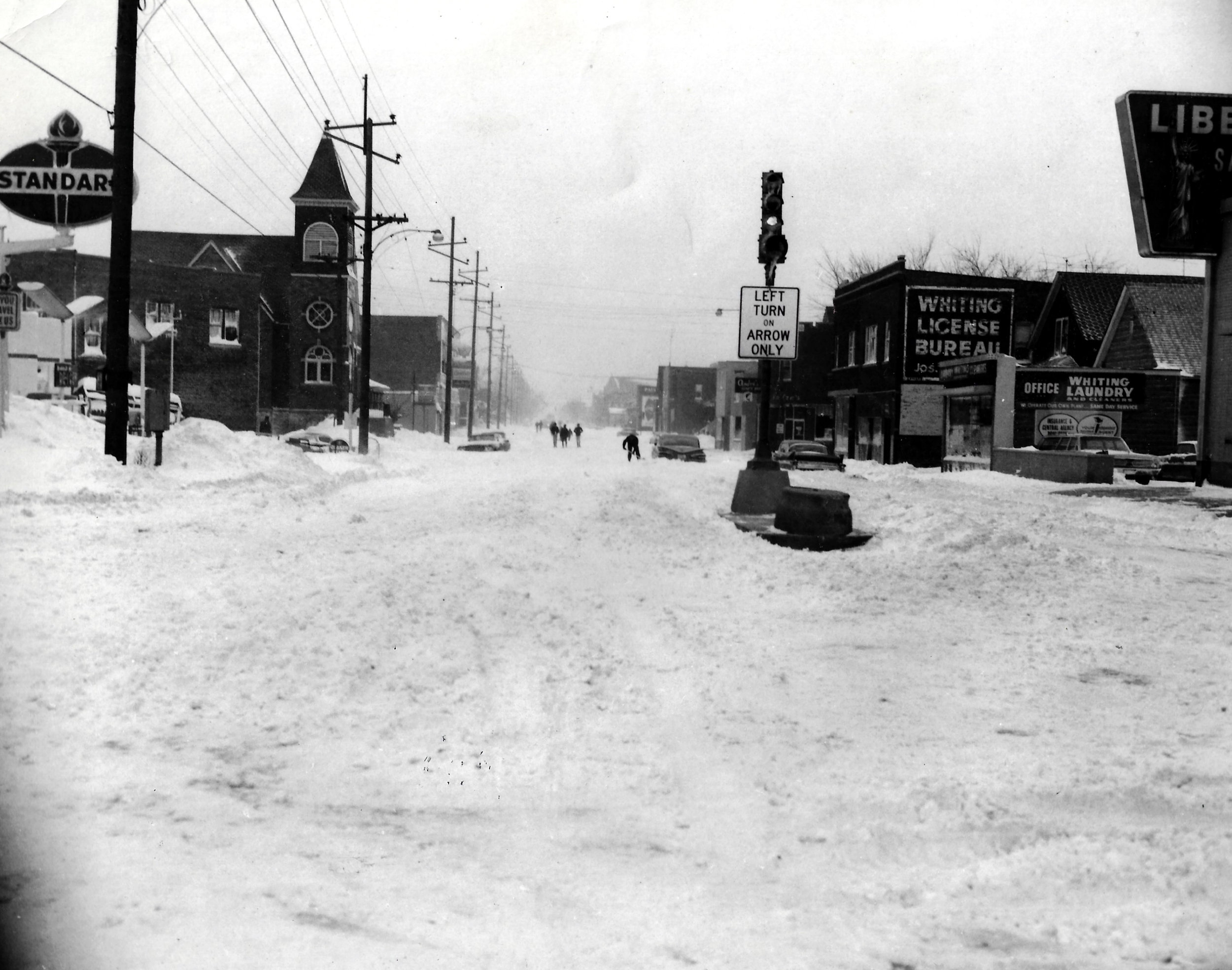 The intersection of 119th Street and Indianapolis Boulevard was not easy to navigate after the snow fell, which is why a group of pedestrians, in the distance, felt comfortable walking down the center of the Boulevard. Closer to the camera, a motorist digs out his car, stuck in the snow on the street.
