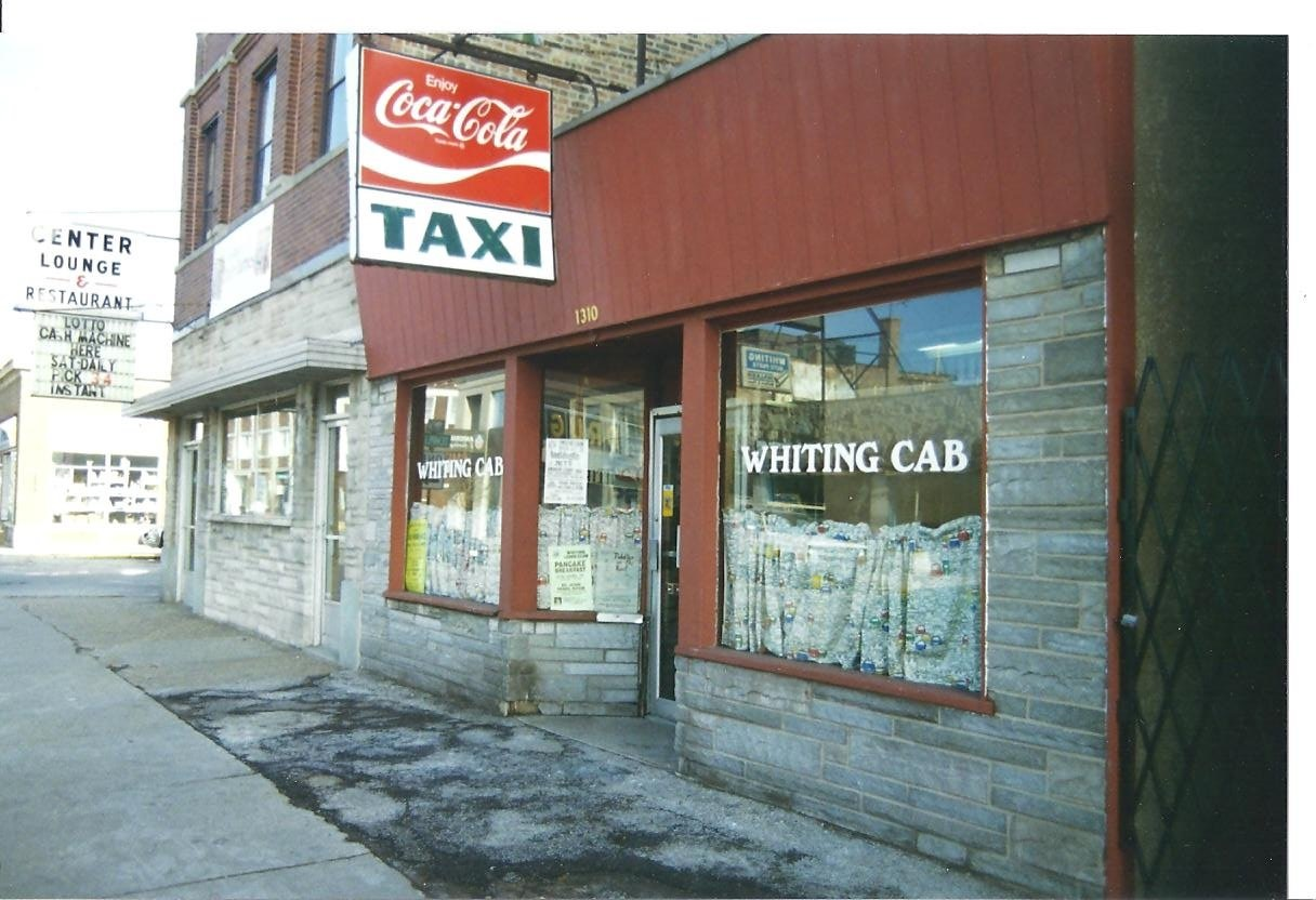 The Taxi Stand, or Whiting Cab, in this 1991 photograph, was located at 1310 119th Street, next door to the Center Lounge. You could get more than a taxi there. Newspapers, magazines, candy, cigarettes and more were on sale inside.