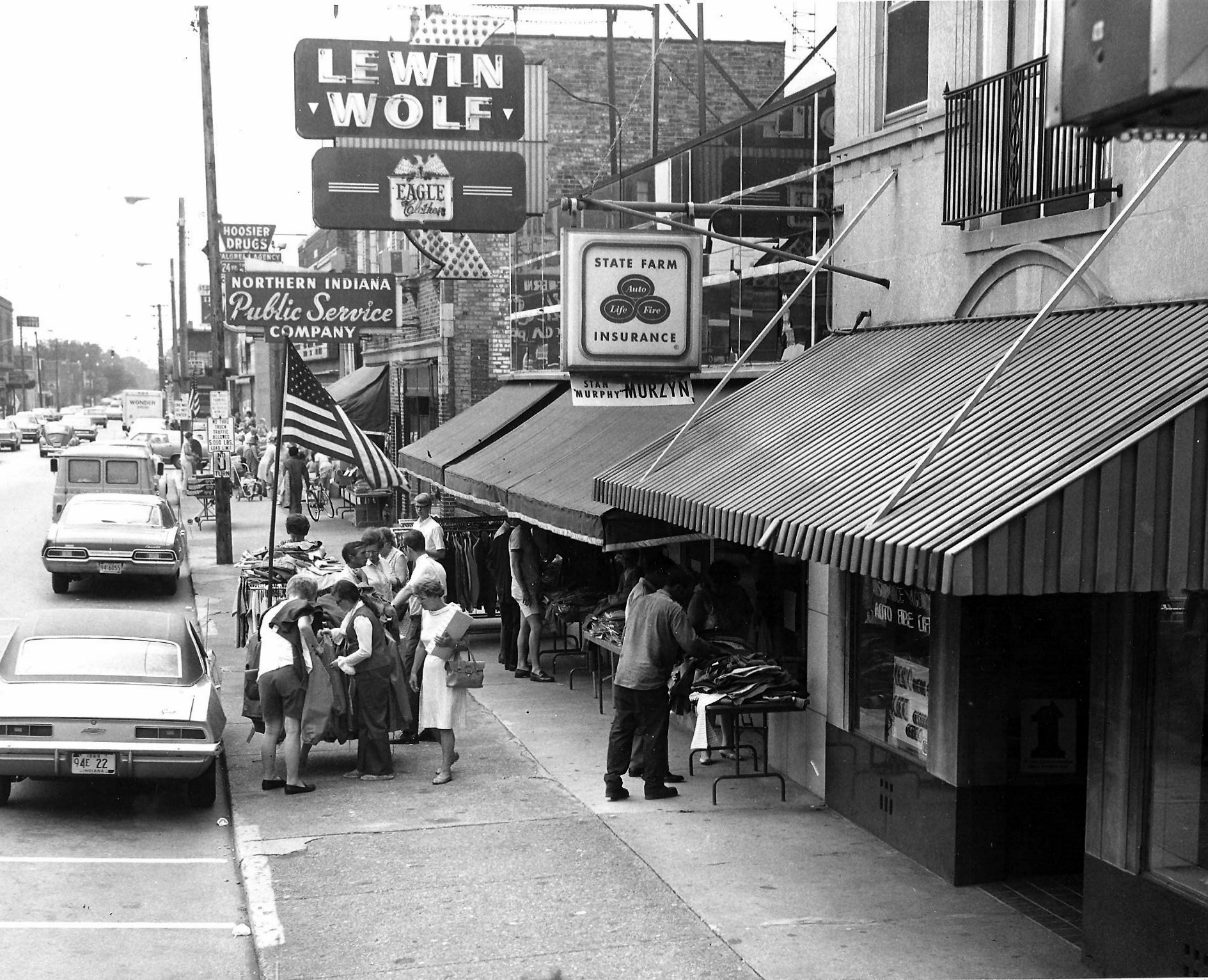 "Shoppers are out for ""Frontier Days,"" a downtown shopping promotion, in 1969. Looking west on 119th Street, the State Farm Insurance office is at 1319 119th Street, with Lewin-Wolf clothing store at 1315, and the NIPSCO office at 1311. (Lovasko Studio photograph)"