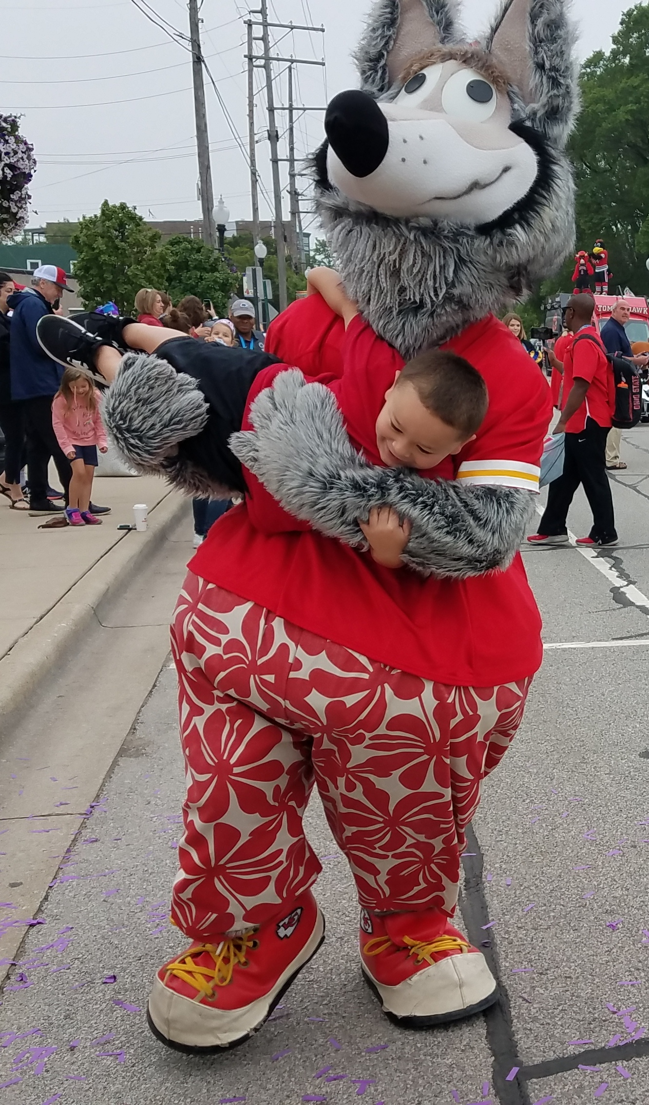 KC Wolf, the mascot of the Kansas City Chiefs, gives a young spectator along the parade route a big hug during the first-ever Mascot Parade in Whiting.