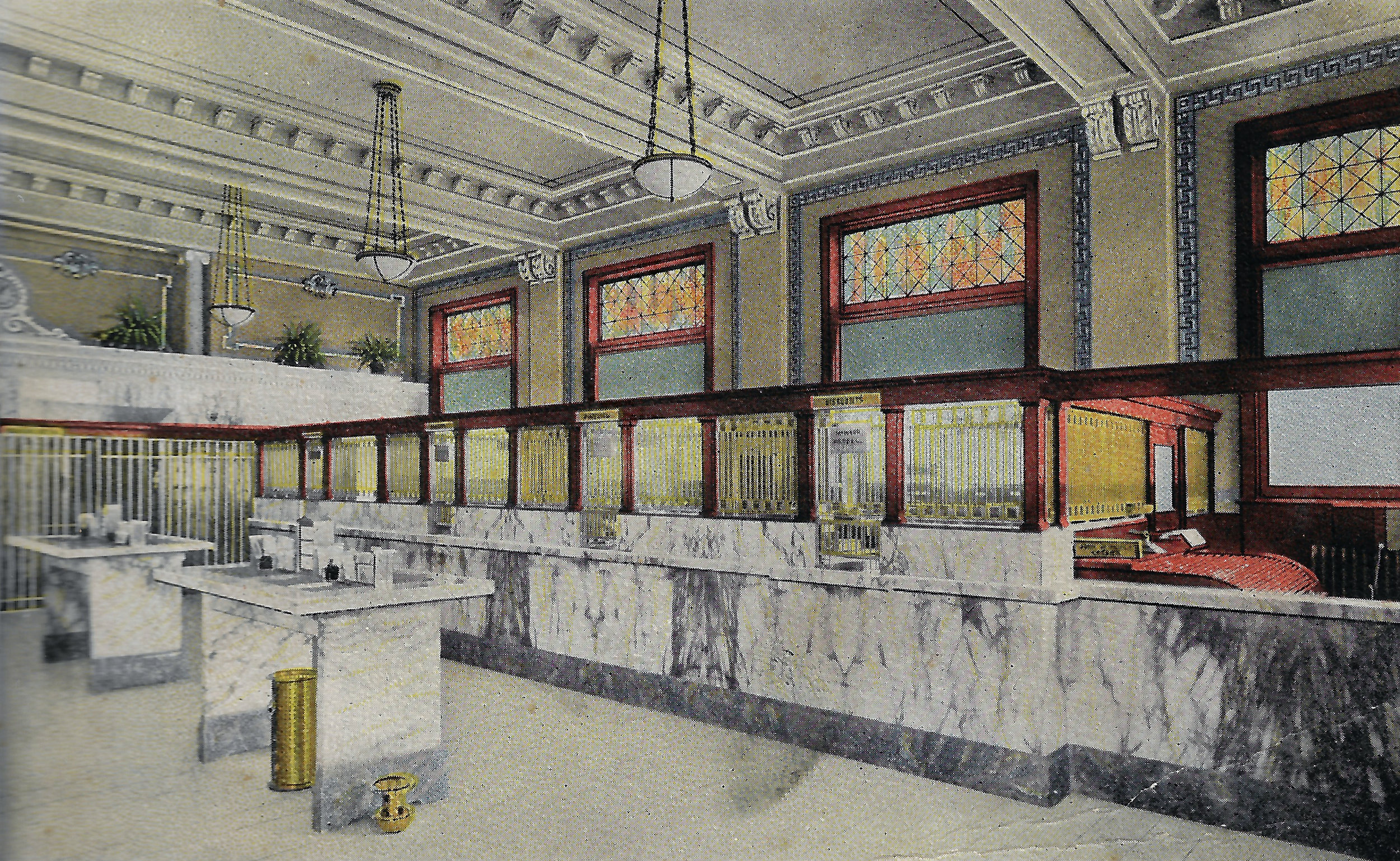 The original interior of the bank featured a good deal of marble and stained glass. At a time when most public buildings were not well lit, the First National Bank had good lighting from its many windows, as well as from the chandeliers hanging from the ceiling. Notice the spittoon for tobacco chewers, located on the floor, next to one of the marble desks for customers.