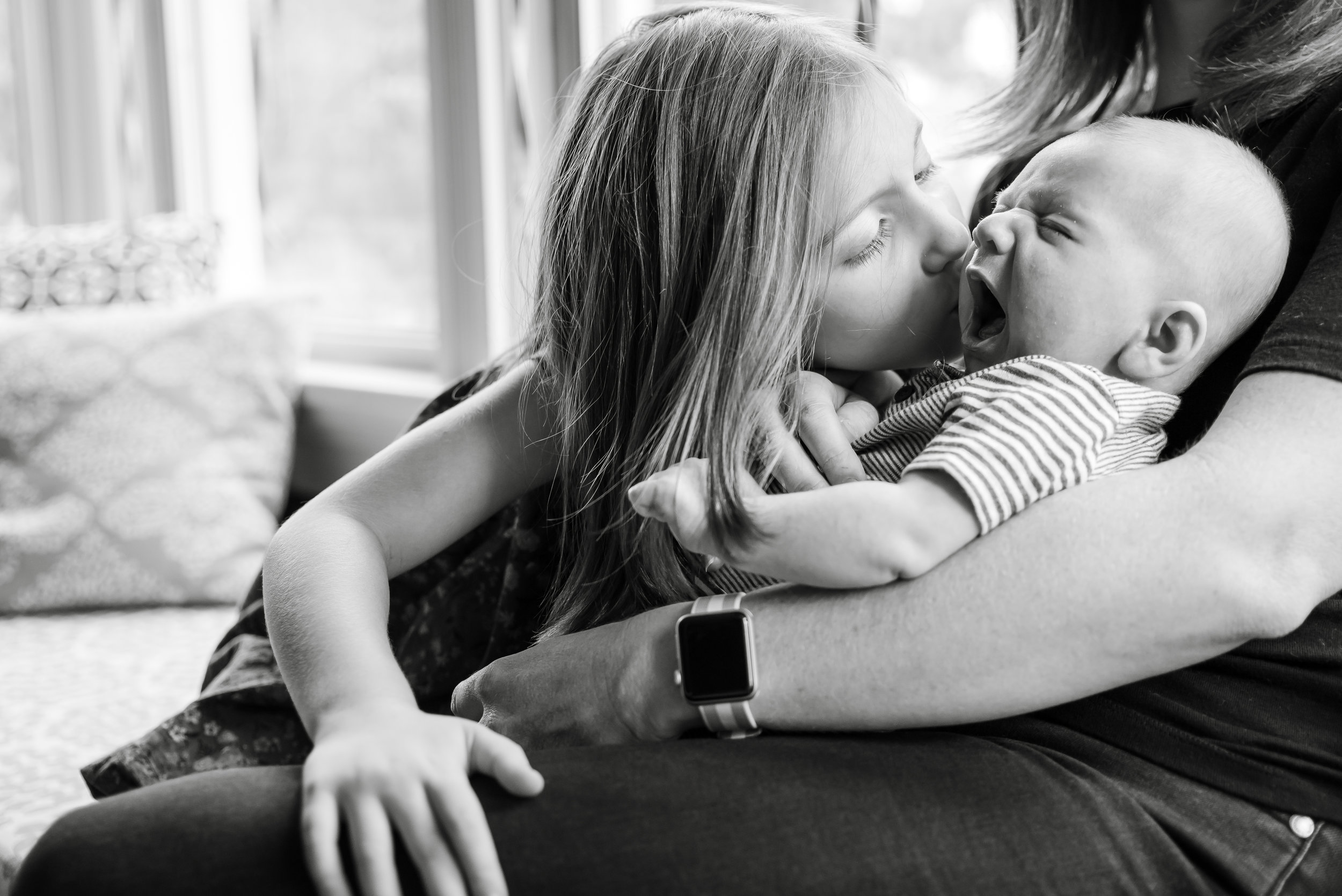 Sibling kissing newborn baby