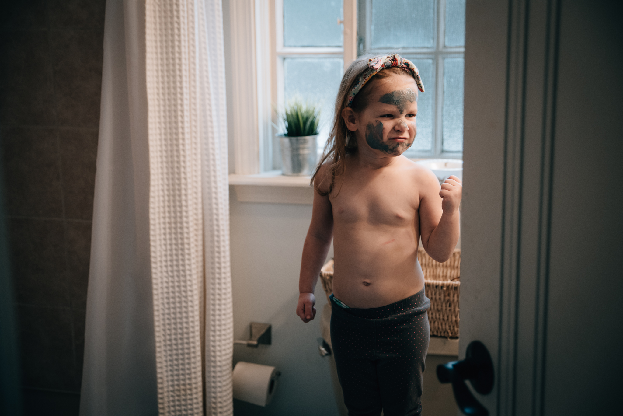 toddler posing in mirror with mud mask