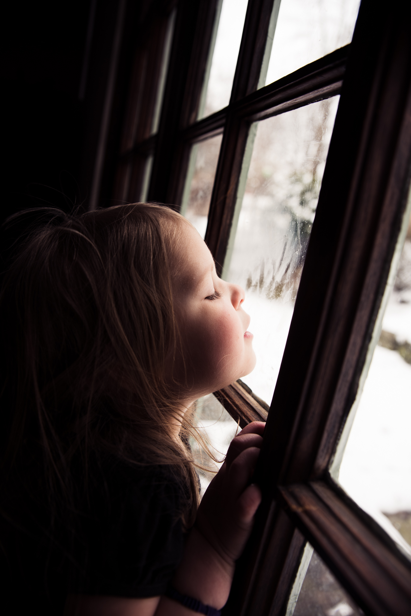 girl looking out winter window