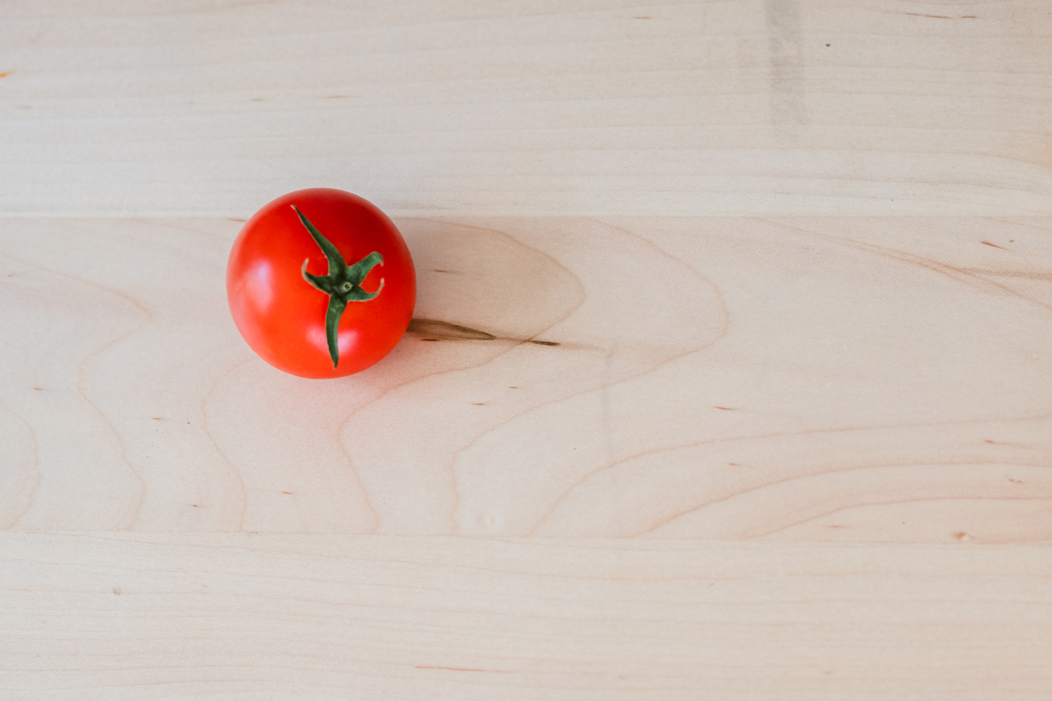 cherry tomato on cutting board