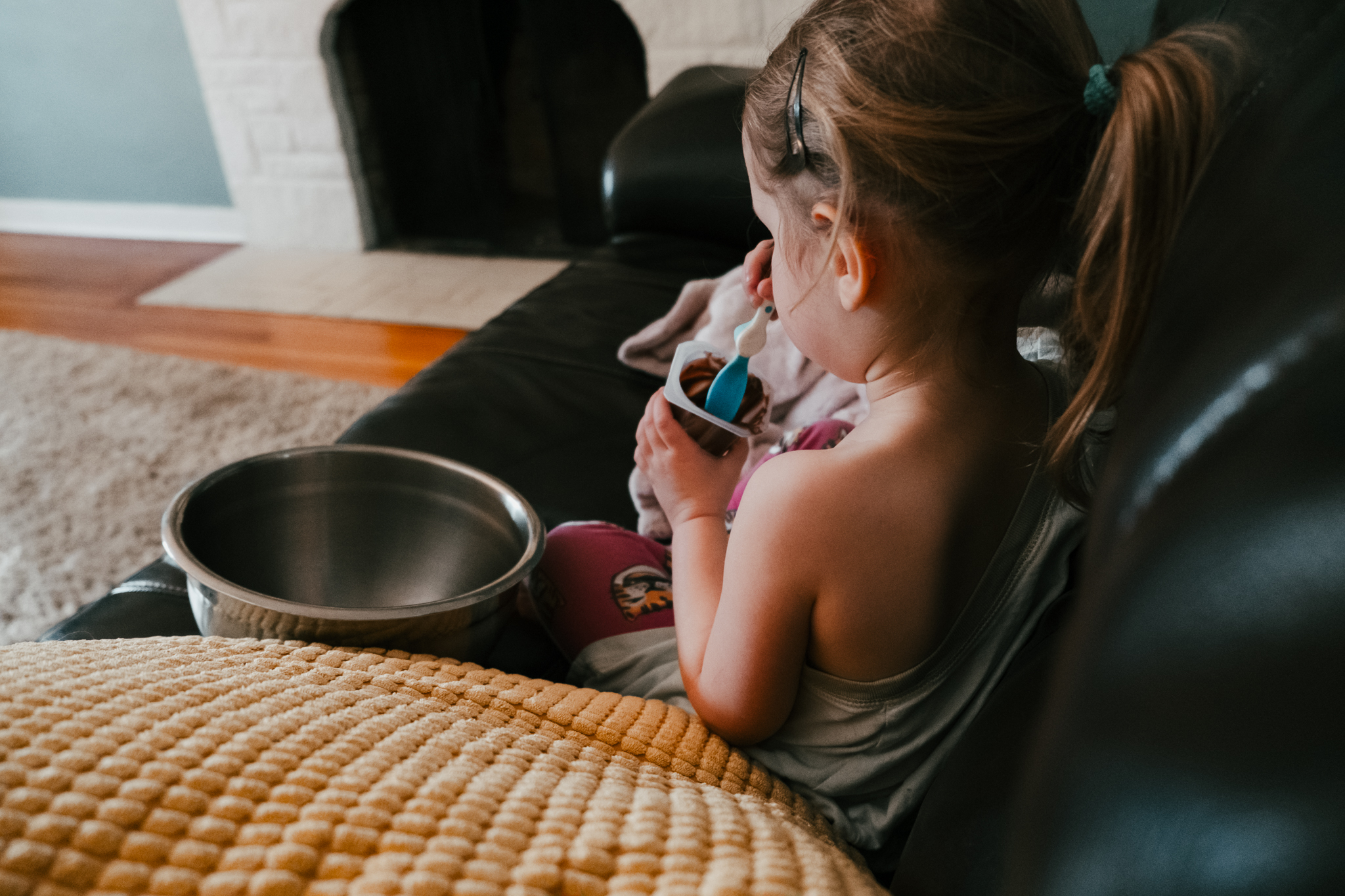 girl eating pudding on couch
