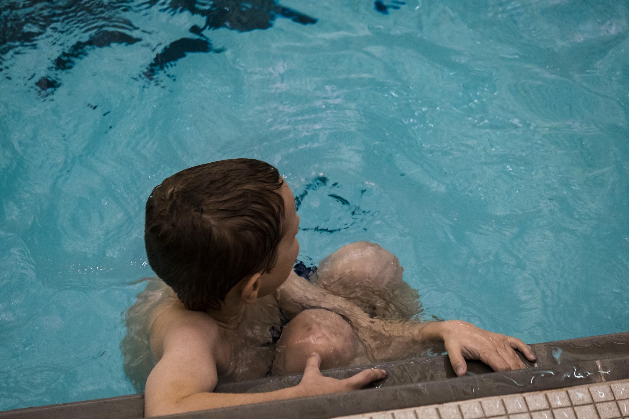 boy in pool swimming classes
