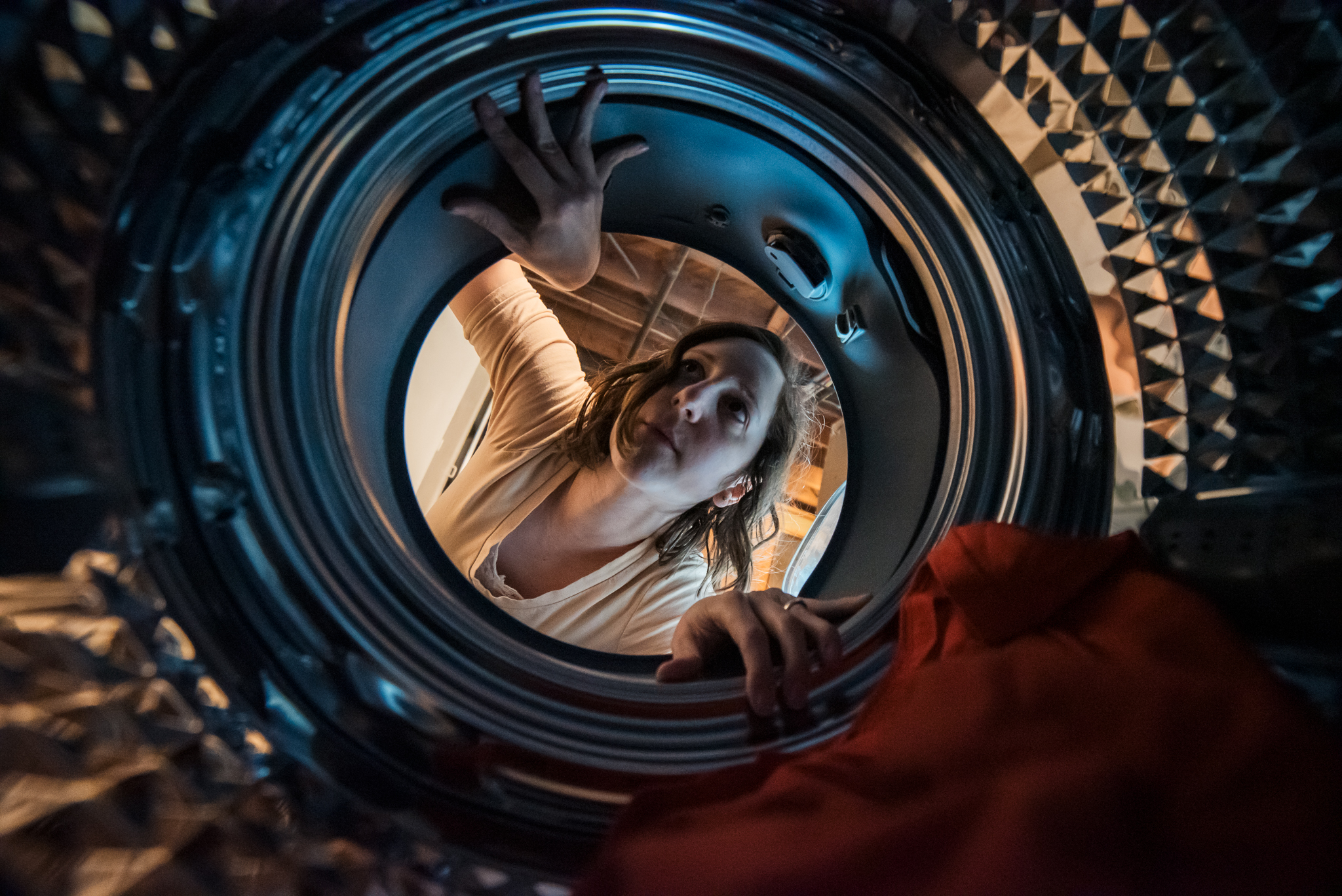 mother looking into dryer doing laundry