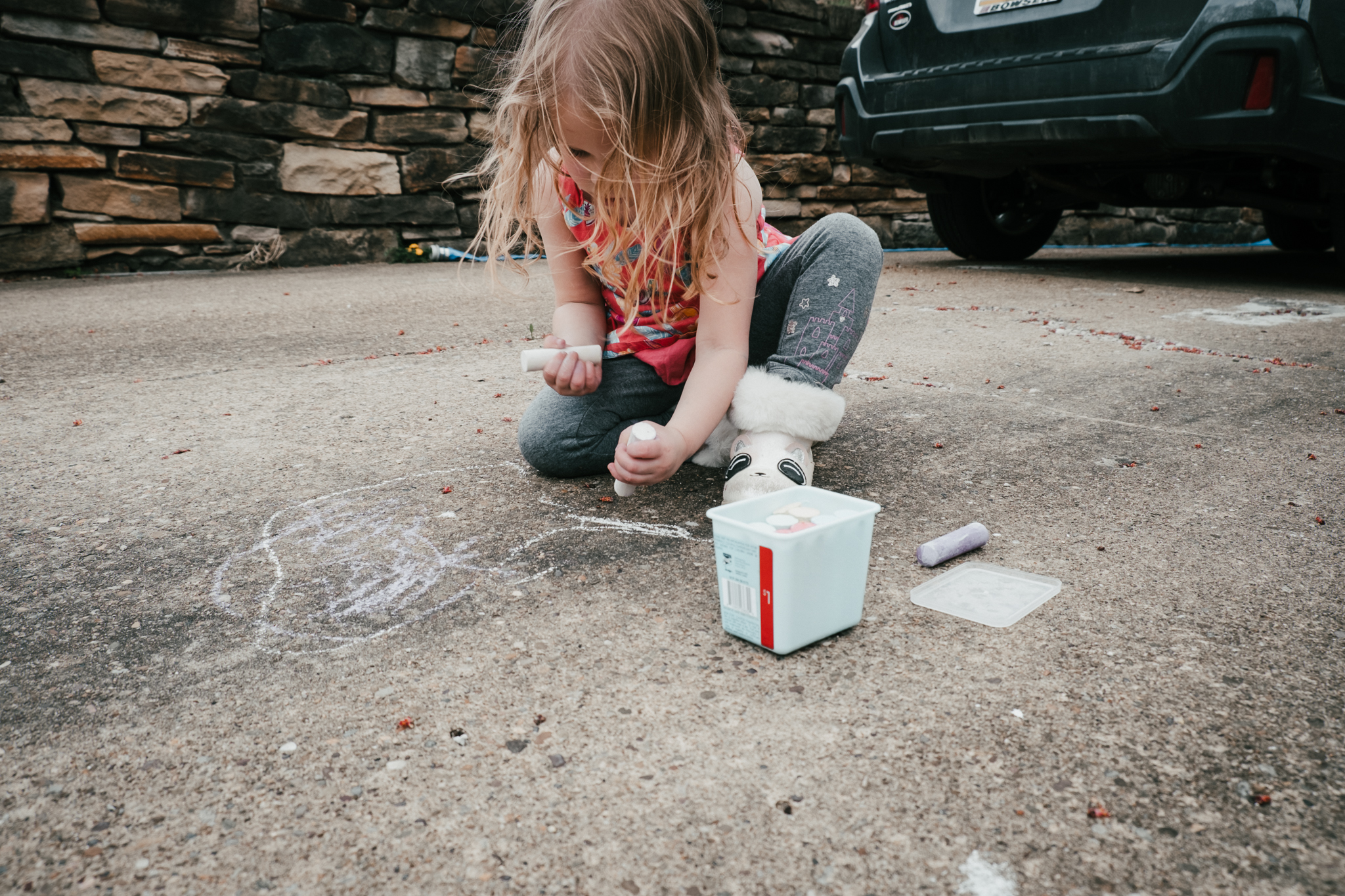child drawing with chalk in driveway