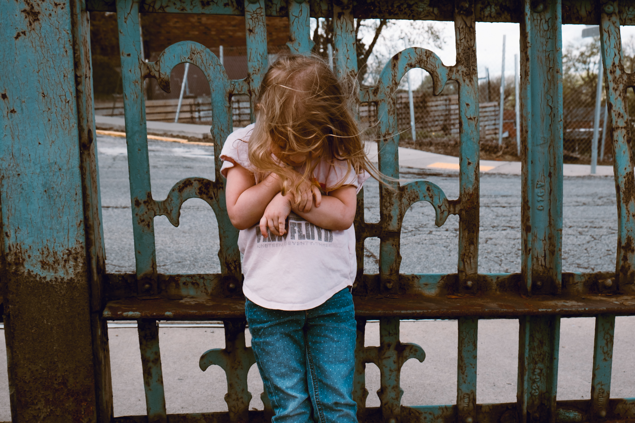 child by rusty blue fence