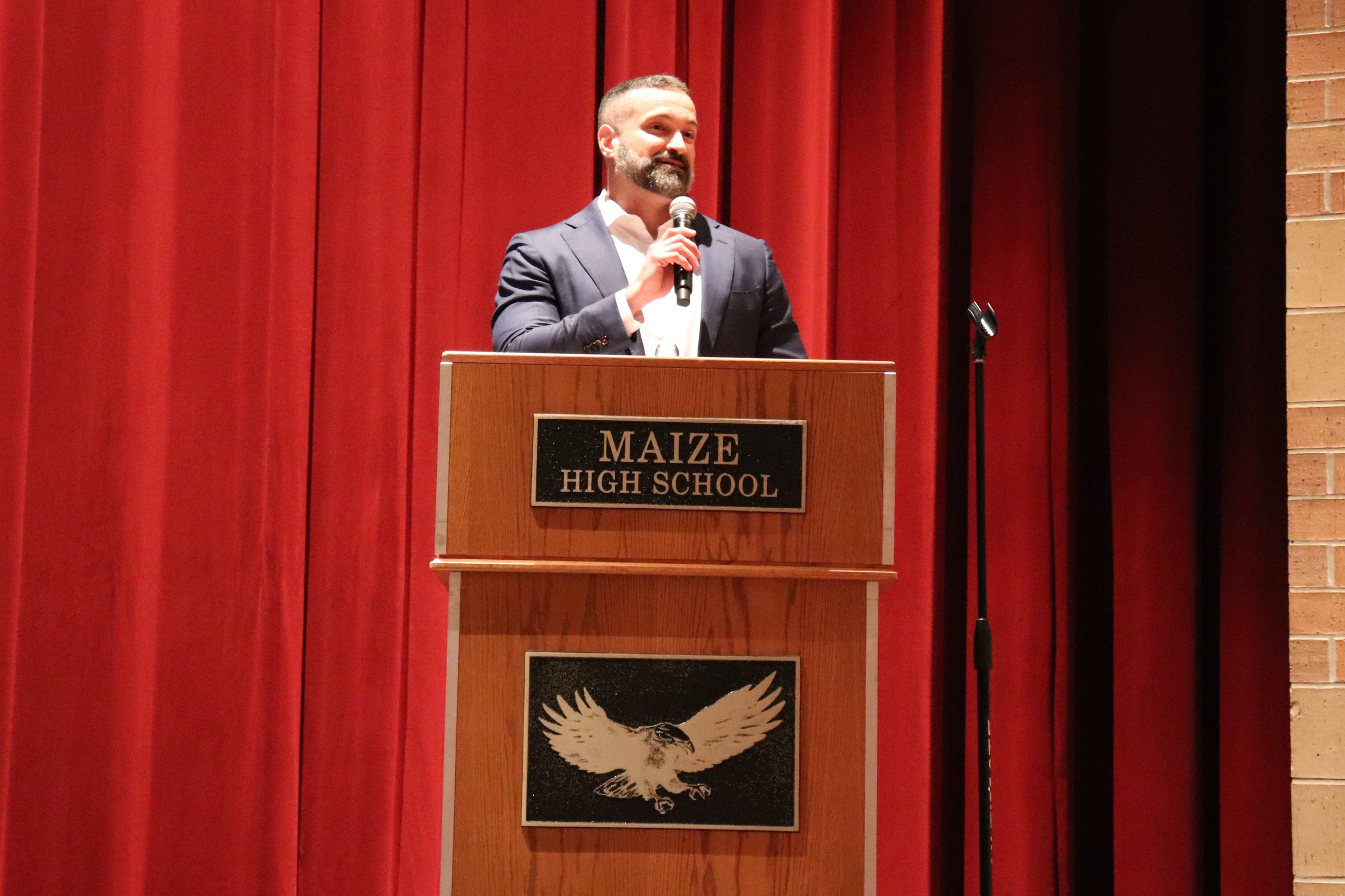 Executive Director Travis Bloom presents this year's grant awards in the all-staff convocation held at Maize High School.