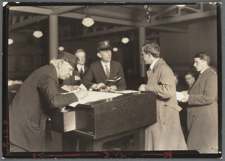 """Interpreter and recorder interviewing newcomers, Ellis Island, New York"". Photograph by Lewis Wickes Hine in 1908. Image Courtesy of New York Public Library Digital Collections."