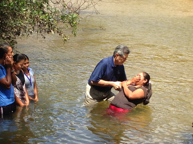 MAG missionary Pastor Carlos Paz baptizing in the Rus Rus River.
