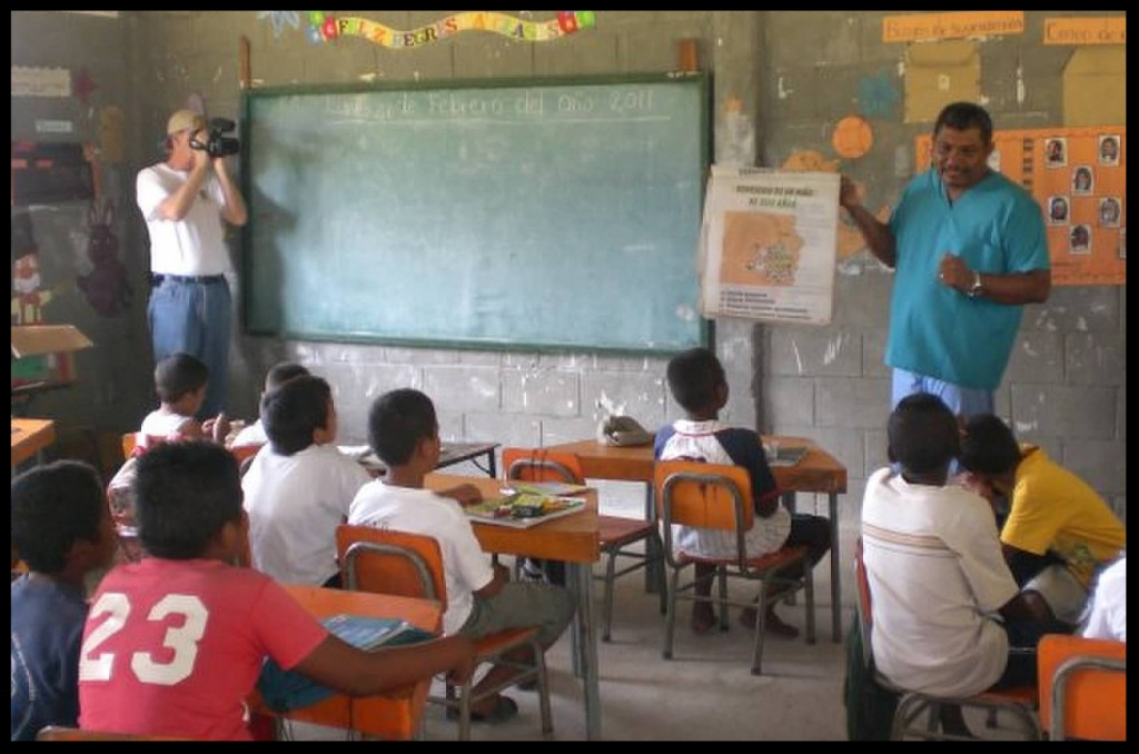 Bobby (in the left corner) shoots video a hygiene education class for children in Rus Rus, Honduras.
