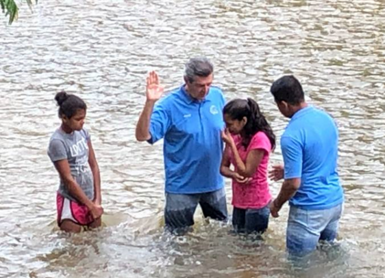 Teen assistants, Niurka and Naomi being baptized in the Rus Rus River.